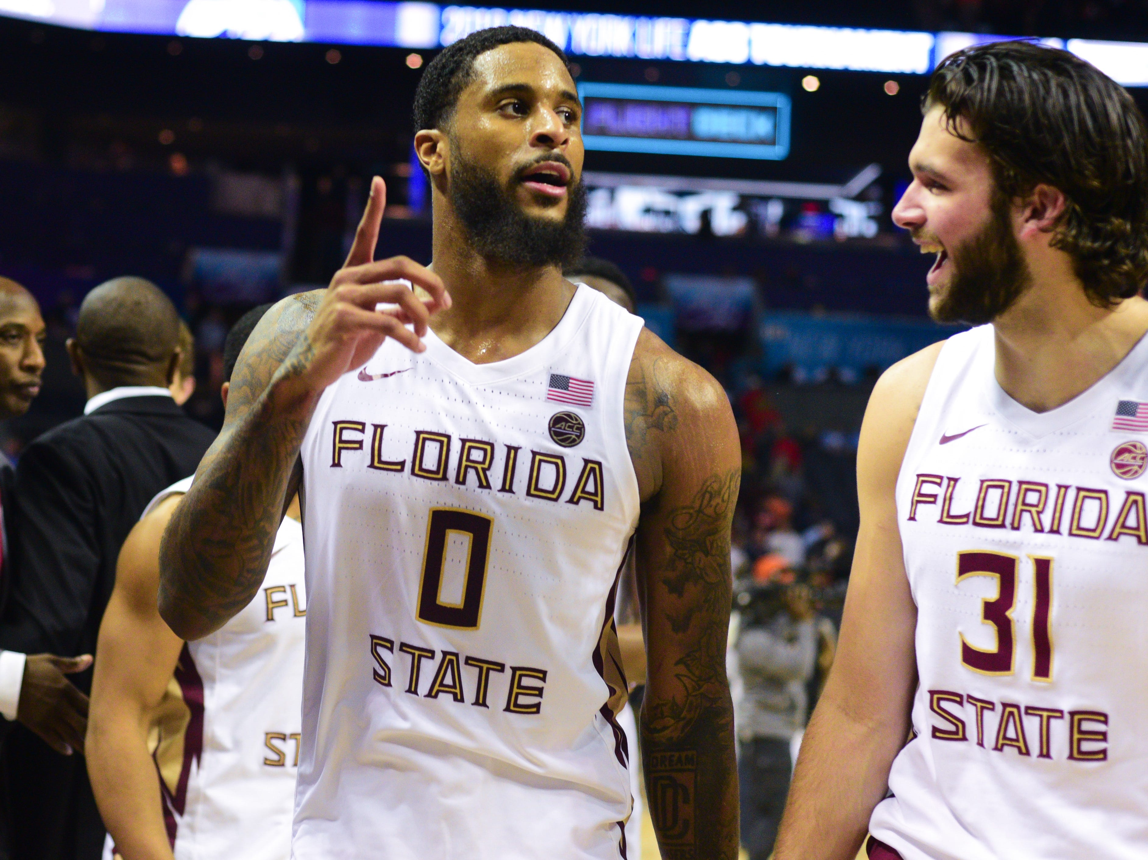 Redshirt senior forward Phil Cofer, left, and sophomore forward Wyatt Wilkes, right, celebrate the Seminoles 65-53 victory over the Virginia Tech Hokies in the ACC Quarterfinal game in Charlotte on Thursday.