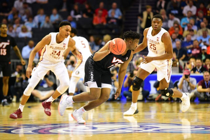 Virginia Tech freshman guard Isaiah Wilkins, center, attempts to breakthrough the Florida State defense during the first half of the ACC Tournament Quarterfinals at the Spectrum Center in Charlotte on Thursday.