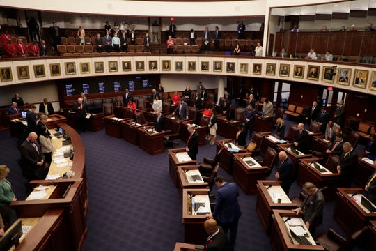 The Florida Senate takes a moment of silence in honor of Angela Drzewiecki, widow of Air Force Staff Sgt. Carl Enis who died in a helicopter crash in Western Iraq, wipes away tears as she and her late husband are recognized at the opening of the Florida Senate session Thursday, March 14, 2019.