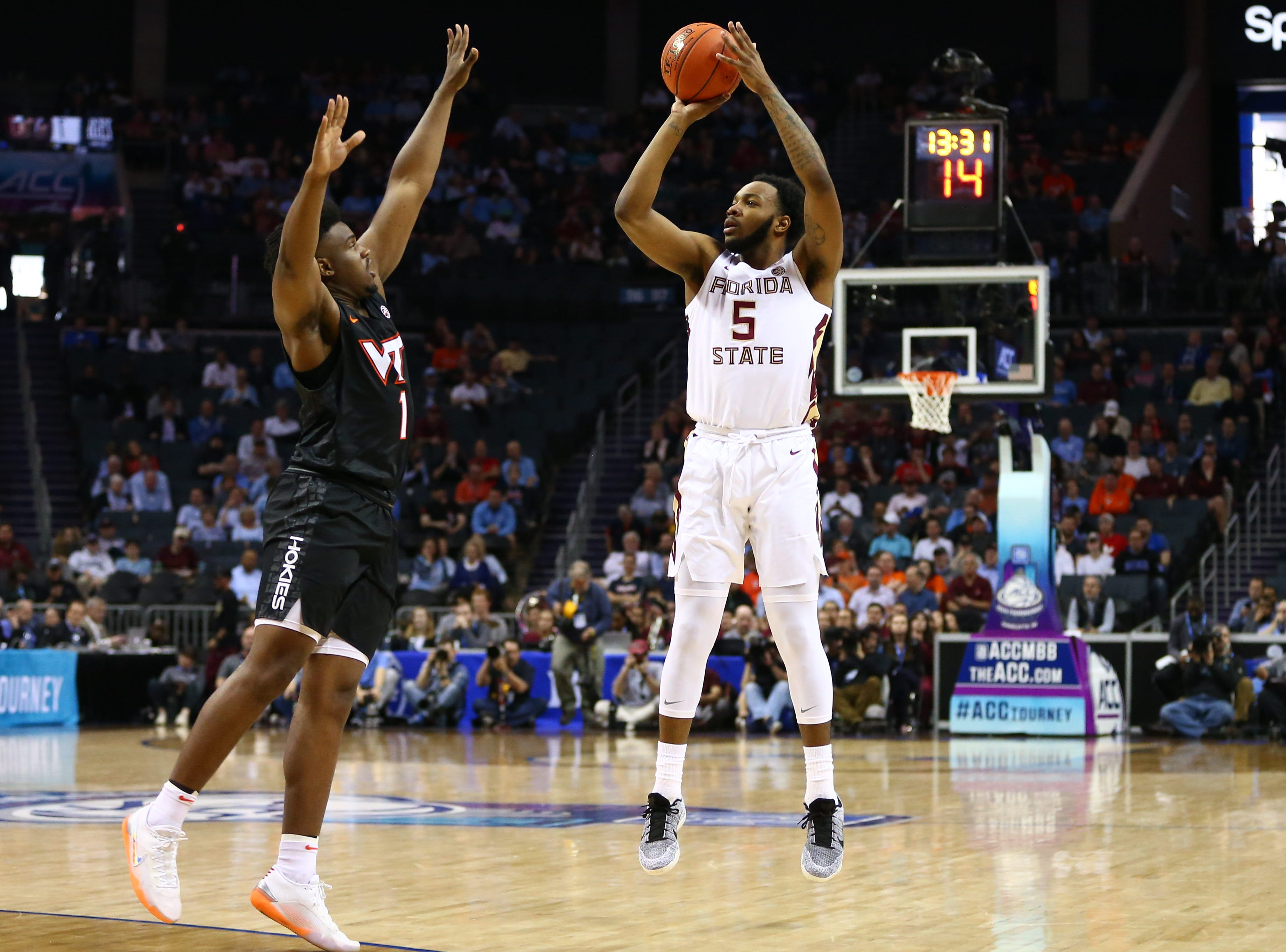 Mar 14, 2019; Charlotte, NC, USA; Florida State Seminoles guard PJ Savoy (5) shoots the ball against Virginia Tech Hokies guard Isaiah Wilkins (1) in the first half in the ACC conference tournament at Spectrum Center. Mandatory Credit: Jeremy Brevard-USA TODAY Sports