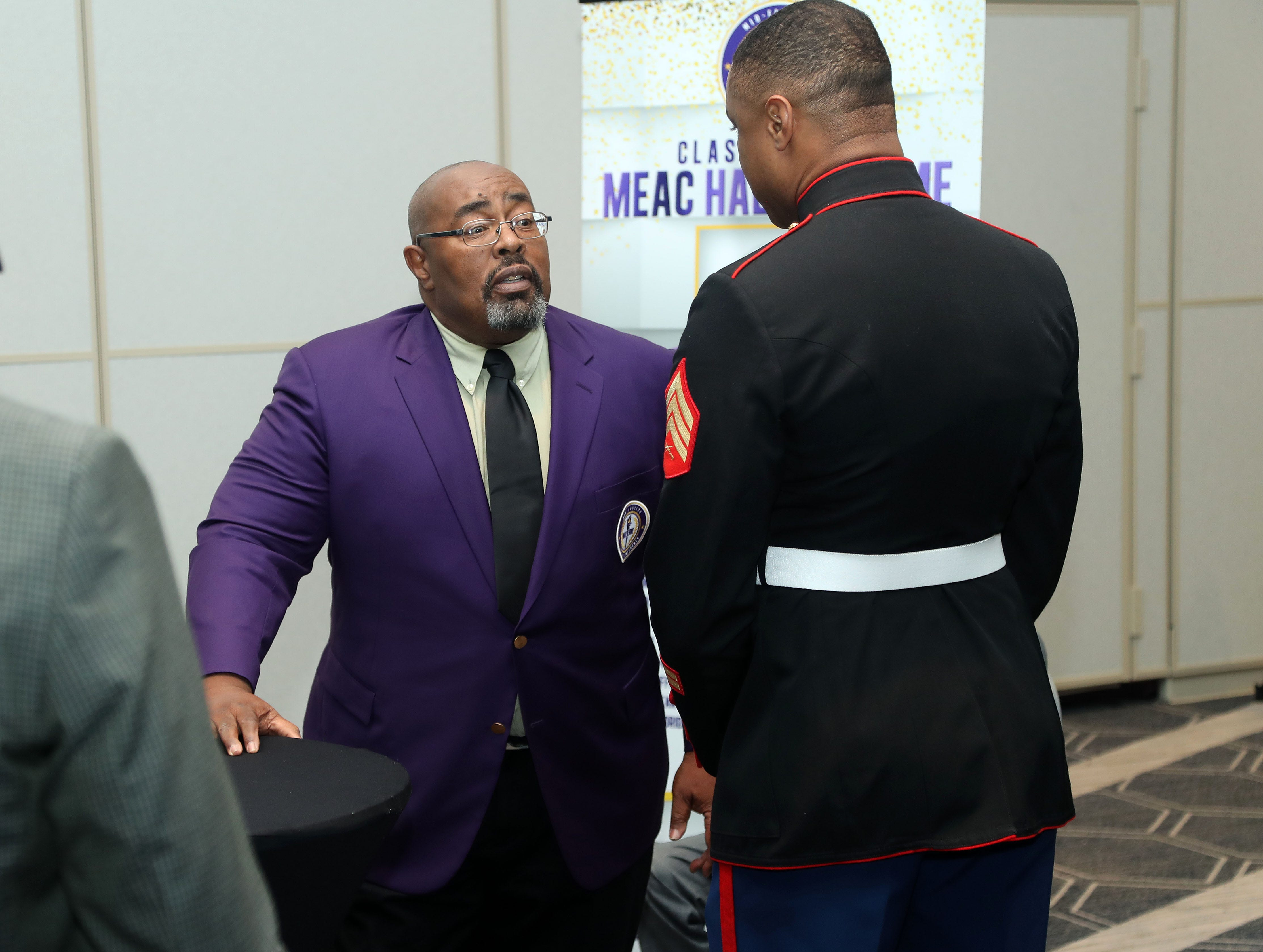 FAMU's Alvin Hollins socializes with a member of the U.S. Marines during the MEAC Hall of Fame enshrinement on Thursday, March 14, 2019 in Norfolk, Virginia.