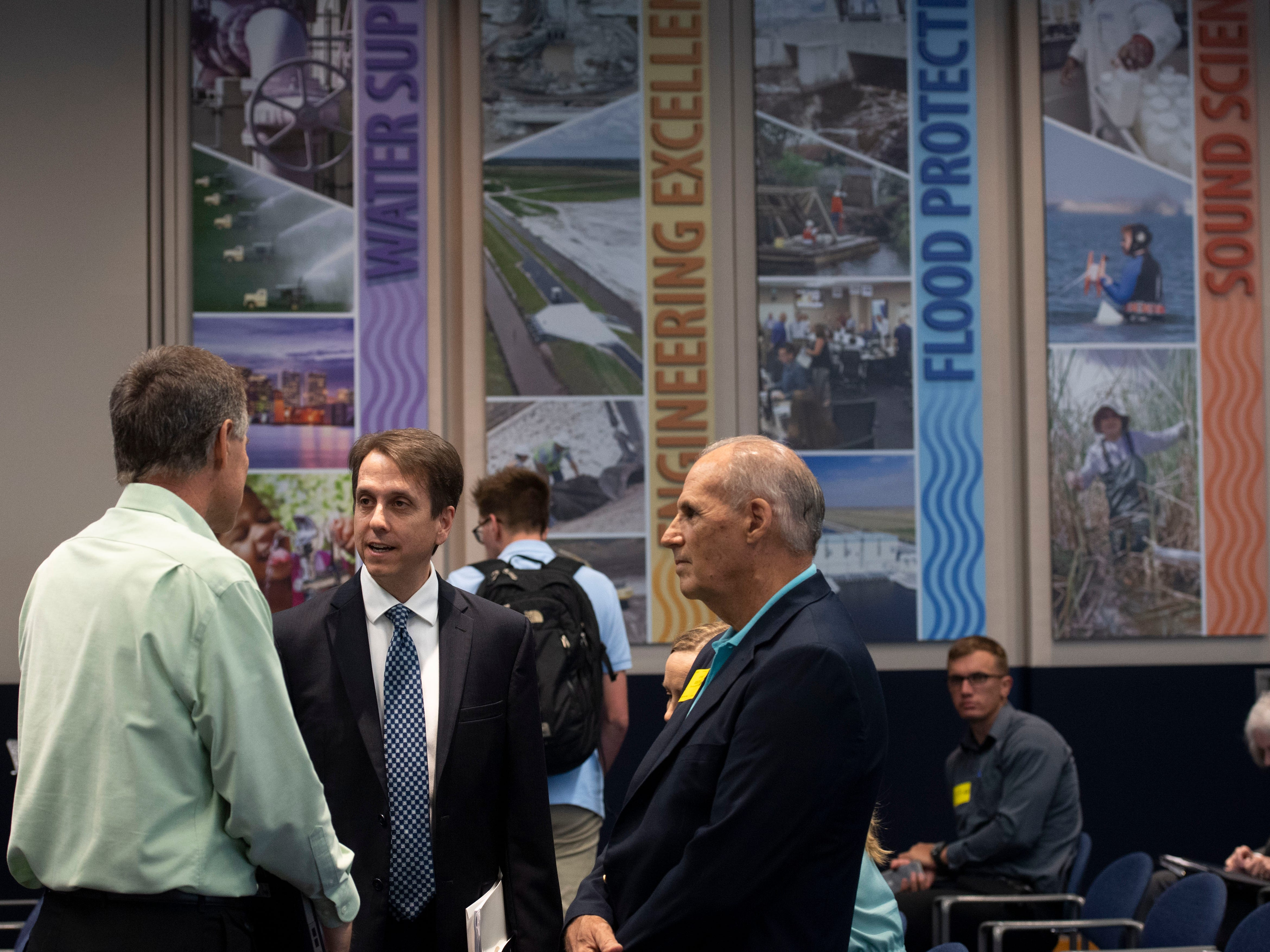 Minutes ahead of his appointment as the executive director of the South Florida Water Management District, Drew Bartlett (center), talks with Gary Goforth (left), an environmental engineer and former district scientist, and Mark Perry, executive director of the Florida Oceanographic Society, on March 14, 2019, at the South Florida Water Management District offices in West Palm Beach. Currently a deputy secretary at Florida's Department of Environmental Protection, Bartlett's reign over the water management district begins April 1.
