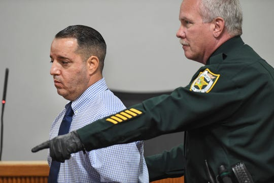 Victor Brancaccio (left) is directed back across the courtroom by a St. Lucie County Sheriff's Office bailiff after being fingerprinted on Thursday, March 14, at the St. Lucie County Courthouse in Fort Pierce after his re-sentencing for the 1993 murder of 81-year-old Mollie Mae Frazier, when he was 16.