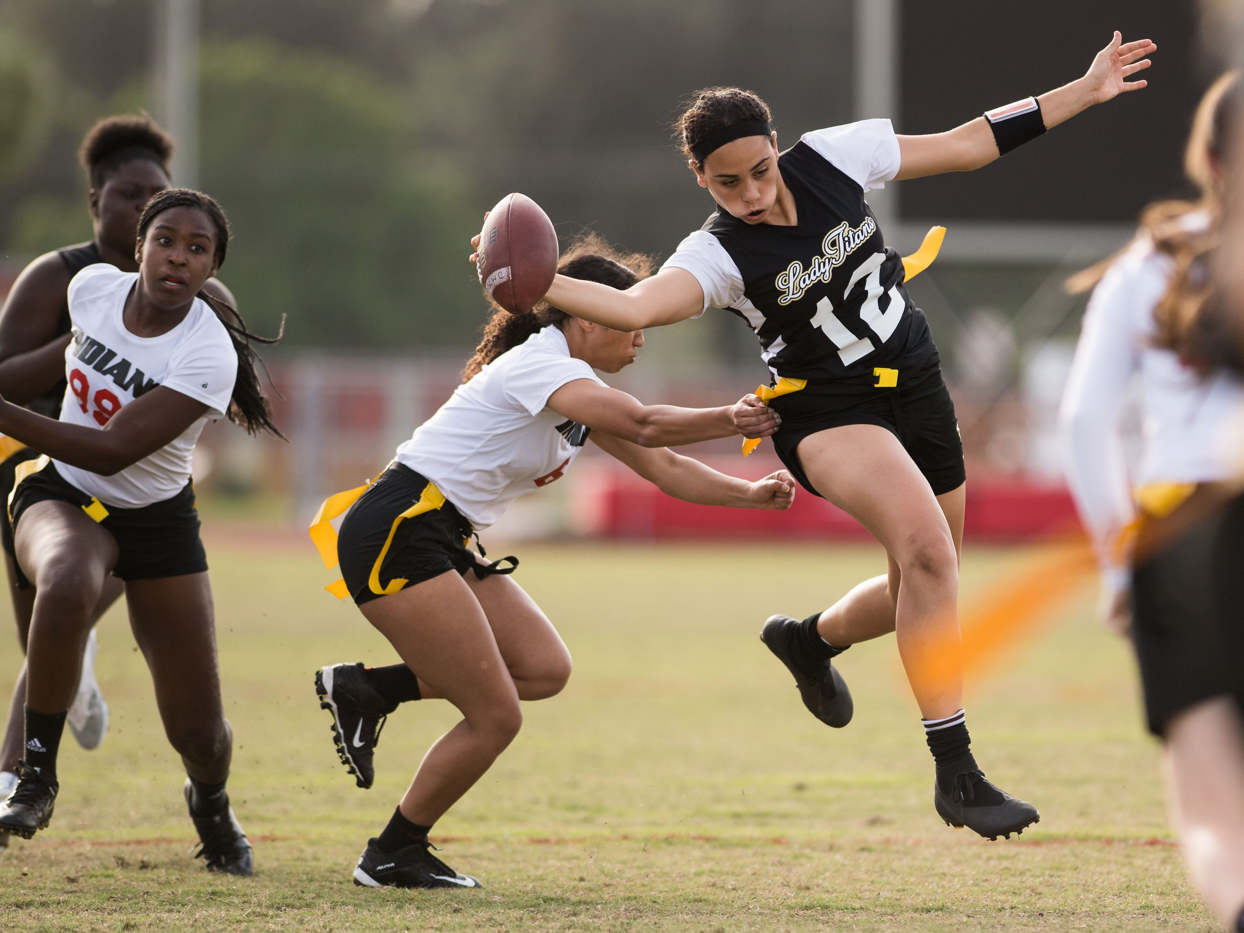 Treasure Coast quarterback Isabella Hernandez leaps to avoid Vero Beach defenders to gain extra yards in the second quarter of the high school flag football game Wednesday, March 13, 2019, at Vero Beach High School.