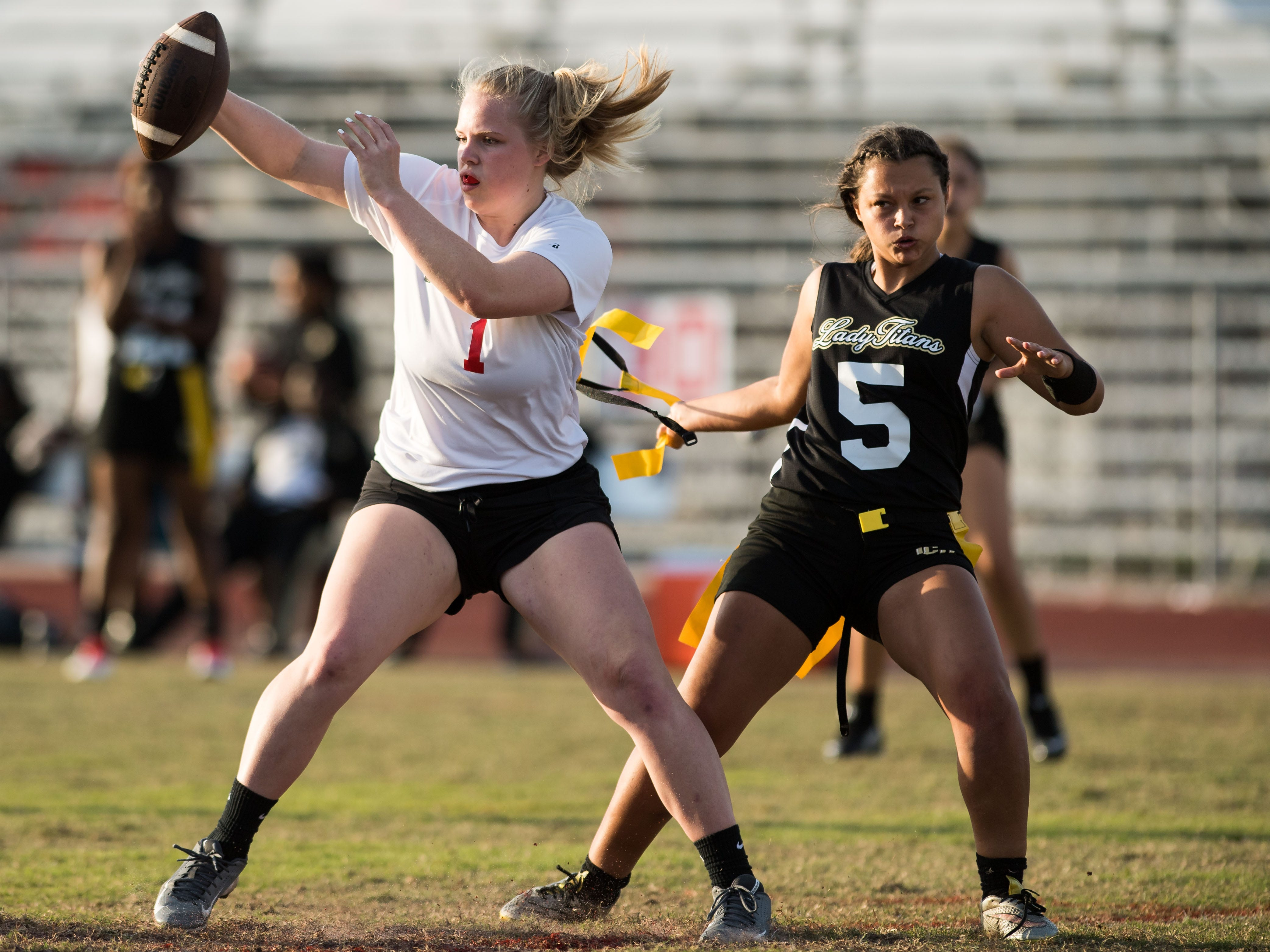 Vero Beach's Audra Teske (left) reaches for extra yards before being downed by Treasure Coast's Victoria Pitsirelos during a drive in the fourth quarter of the high school flag football game Wednesday, March 13, 2019, at Vero Beach High School. Vero couldn't score on the drive, and lost 20-13 to Treasure Coast.