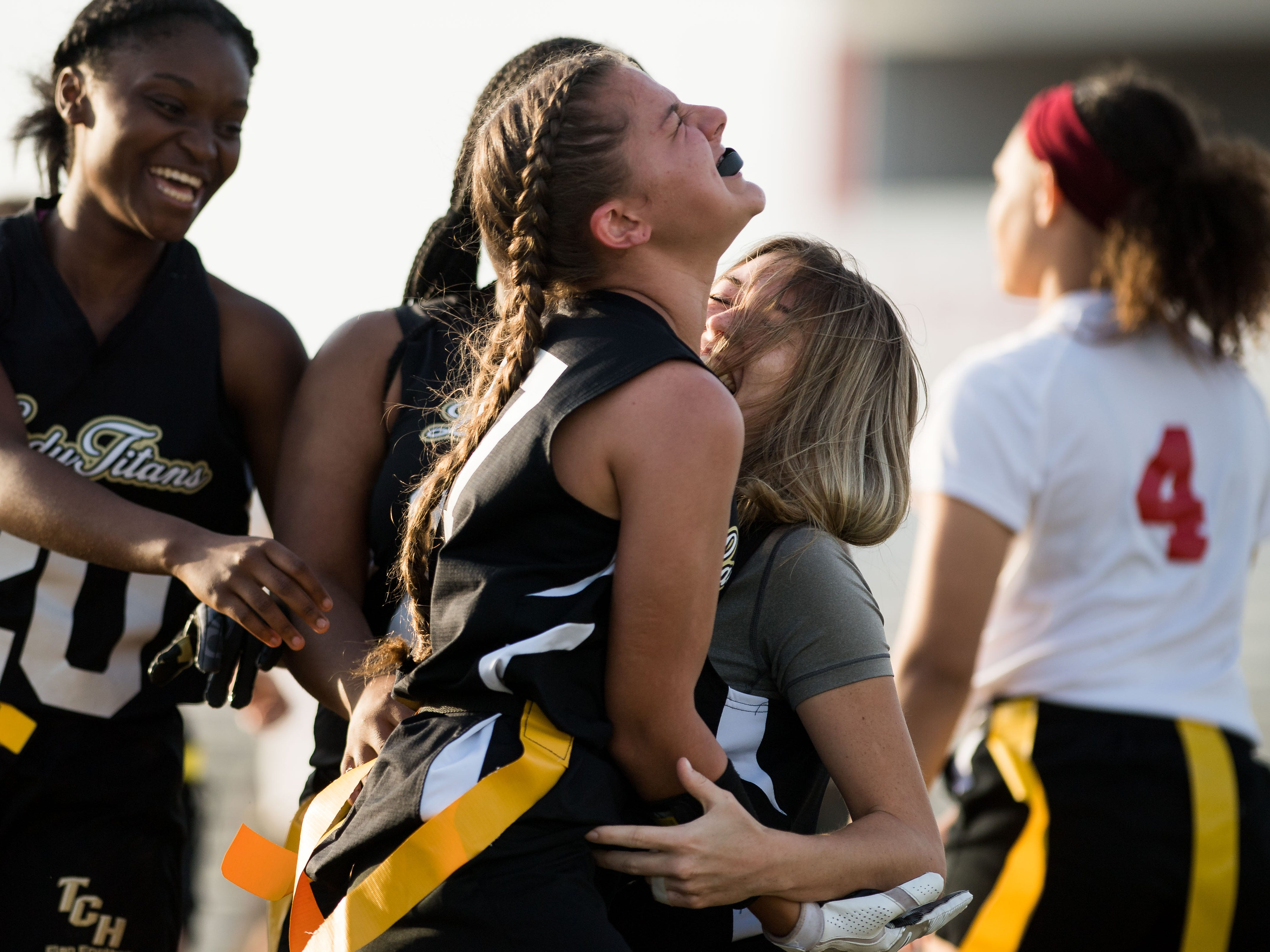 Treasure Coast's Valentina Breault (center) congratulates teammate Savannah Hawthorne (right) for catching the game-winning touchdown in the fourth quarter against Vero Beach during the high school flag football game Wednesday, March 13, 2019, at Vero Beach High School. Teammate Tianne Blagrove (far left) also reaches in for a hug.