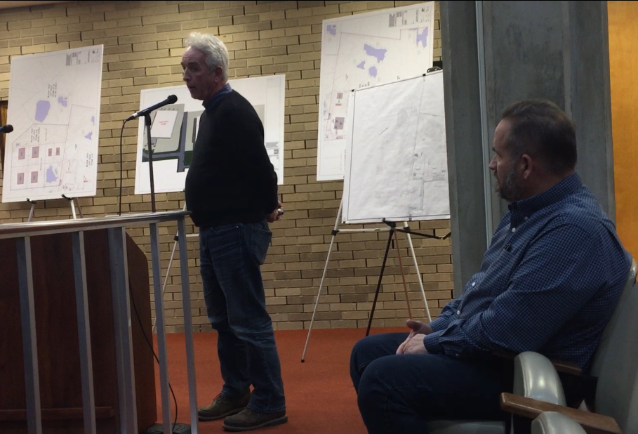 Paul Riggins, owner of Riggins Oil Co., speaks at a Vineland Planning Board meeting Wednesday night in favor of an industrial park site plan submitted by Northeast Precast LLC. Seated is John Ruga, owner of Northeast Precast.
