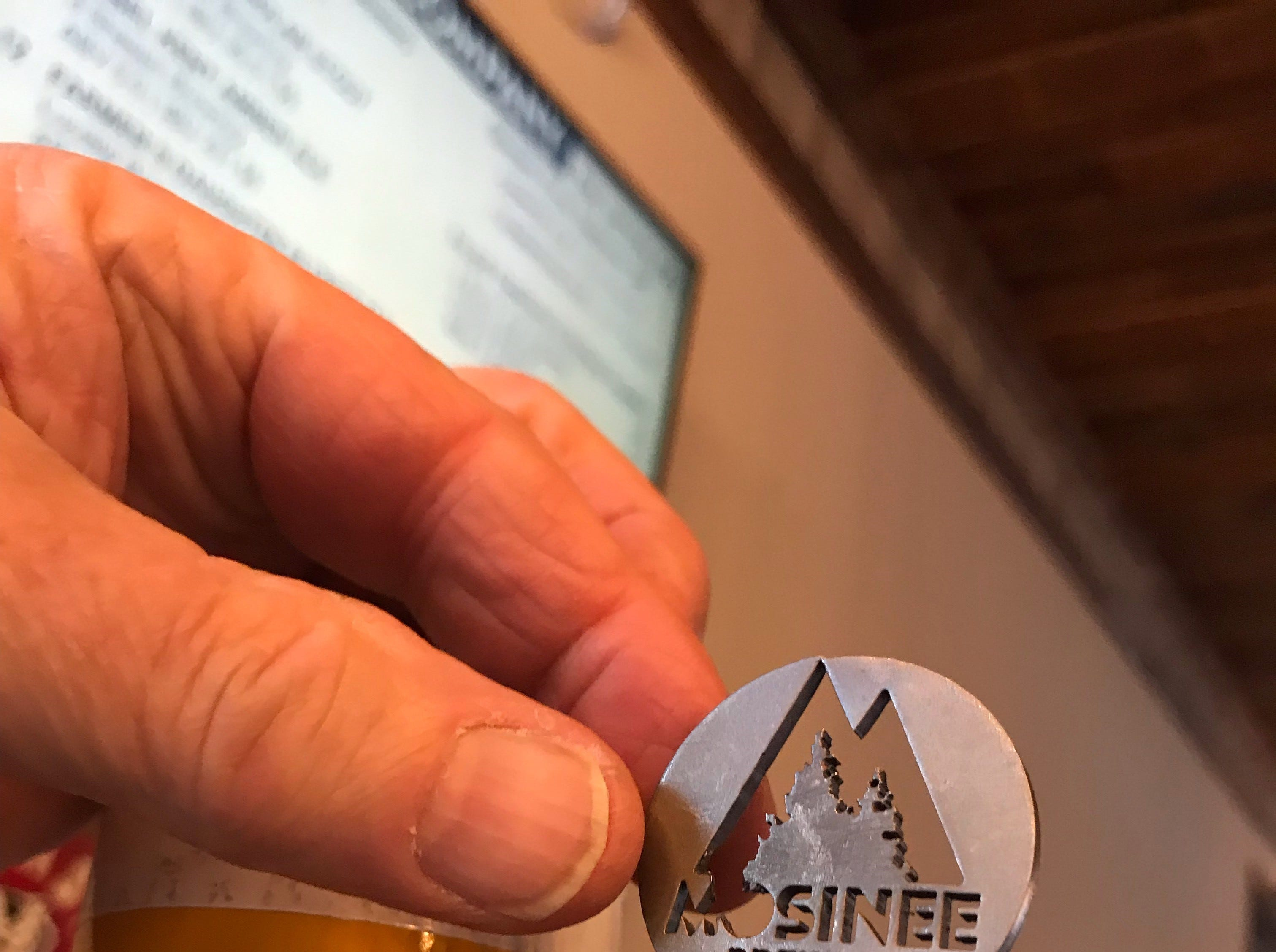 """A logo for Mosinee Brewing Company displayed on top of a tap handle. The brewery is considering using a fire hose as the tap handle for its upcoming """"Flashover Red"""" brew, in honor of the Mosinee Fire Department."""