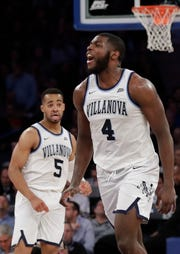 Villanova's Eric Paschall (4) celebrates after scoring as teammate Phil Booth (5) watches during the second half of an NCAA college basketball game against Providence in the Big East Conference tournament Thursday, March 14, 2019, in New York. Villanova won 73-62.