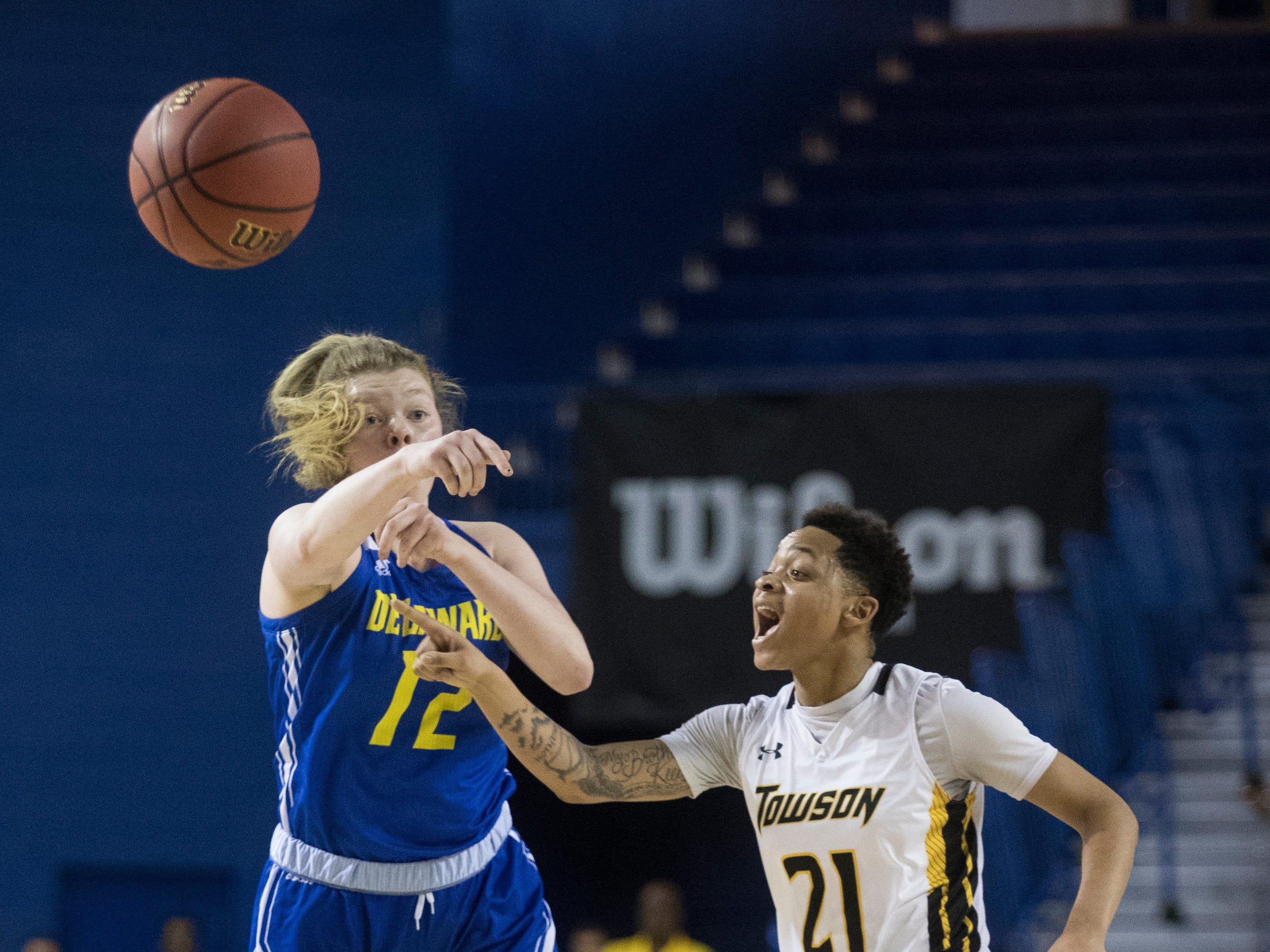 Delaware's Lizzie Oleary (12) passes to a teammate during their CAA quarterfinal against Towson. Towson defeated Delaware 59-49.