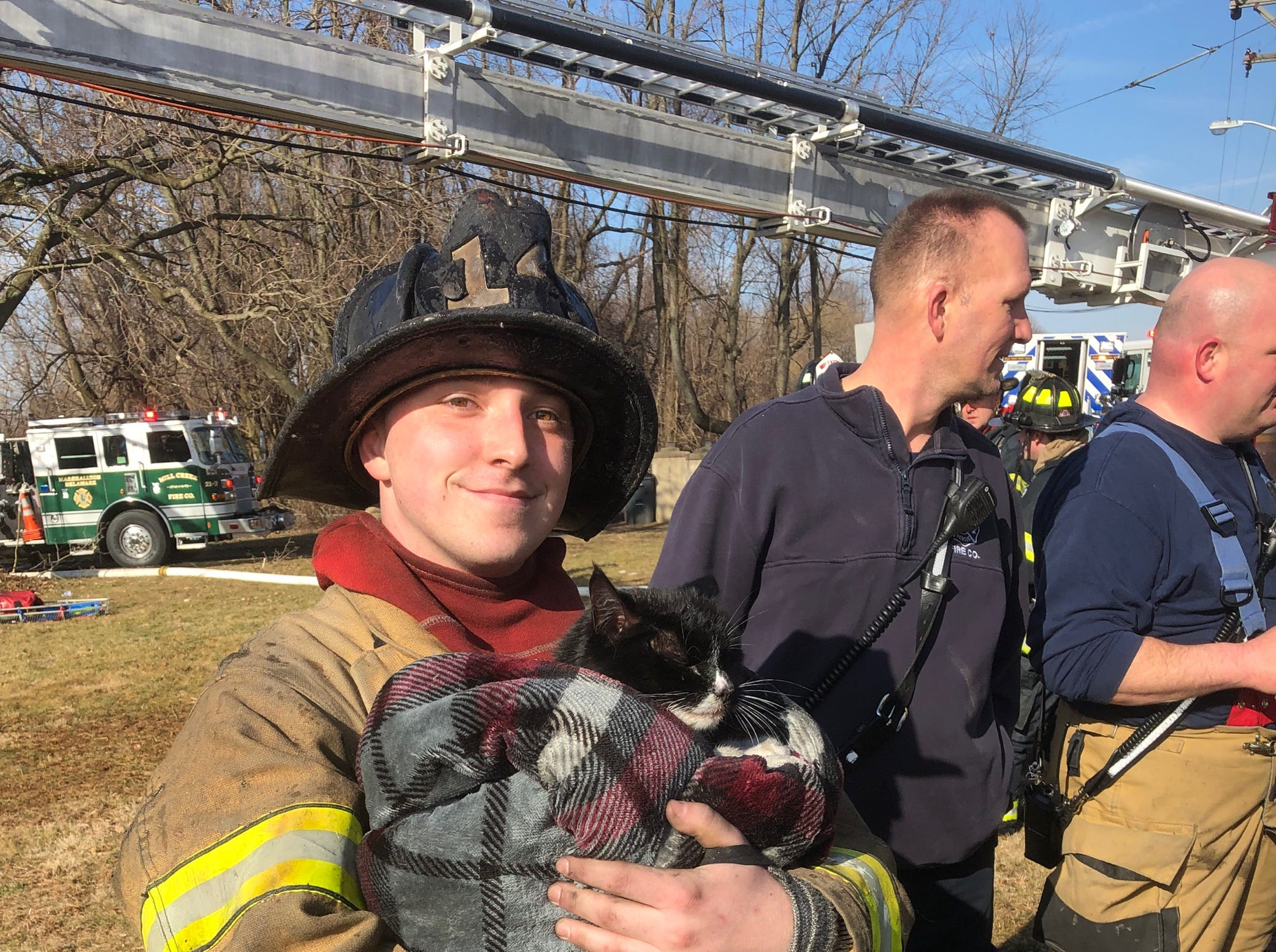 A firefighter holds a cat rescued from a house fire in Milltown.