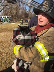 A firefighter holds a cat rescued from a house fire in Millville on Thursday.