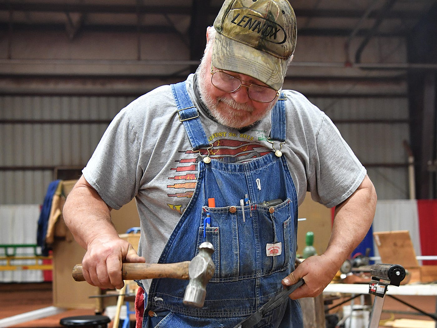 Russell Martin hammers on some red-hot steel as he forges a hook during a blacksmithing demonstration Thursday morning at the Wichita Falls Ranch and Farm Expo at the Bridwell Ag Center.