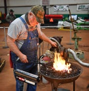 Russell Martin, an apprentice blacksmith, heats a piece of steel in a coal-fired forge Thursday morning at the Wichita Falls Ranch and Farm Expo at the Bridwell Ag Center.