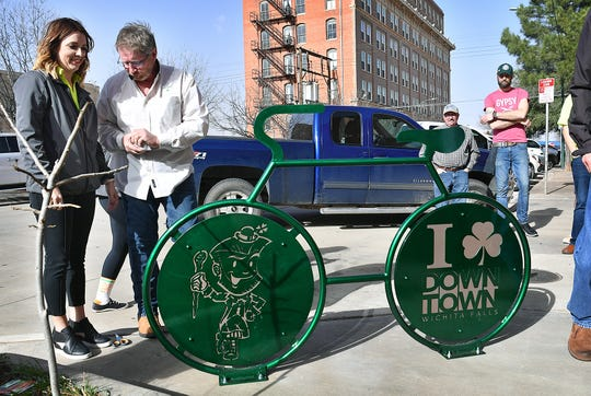 Downtown Wichita Falls Development Executive Director Jana Schmader talks with board member John Dickenson at the unveiling of the latest sculptural bike rack downtown at 8th and Indiana. The rack was donated by the Iron Horse Pub and Union Square Credit Union.