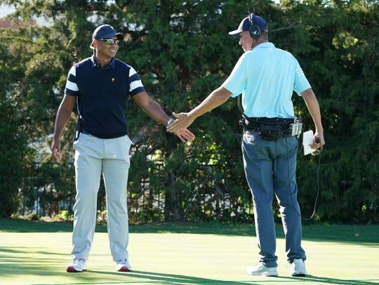 Tiger Woods slaps hands with Jim Mackay.