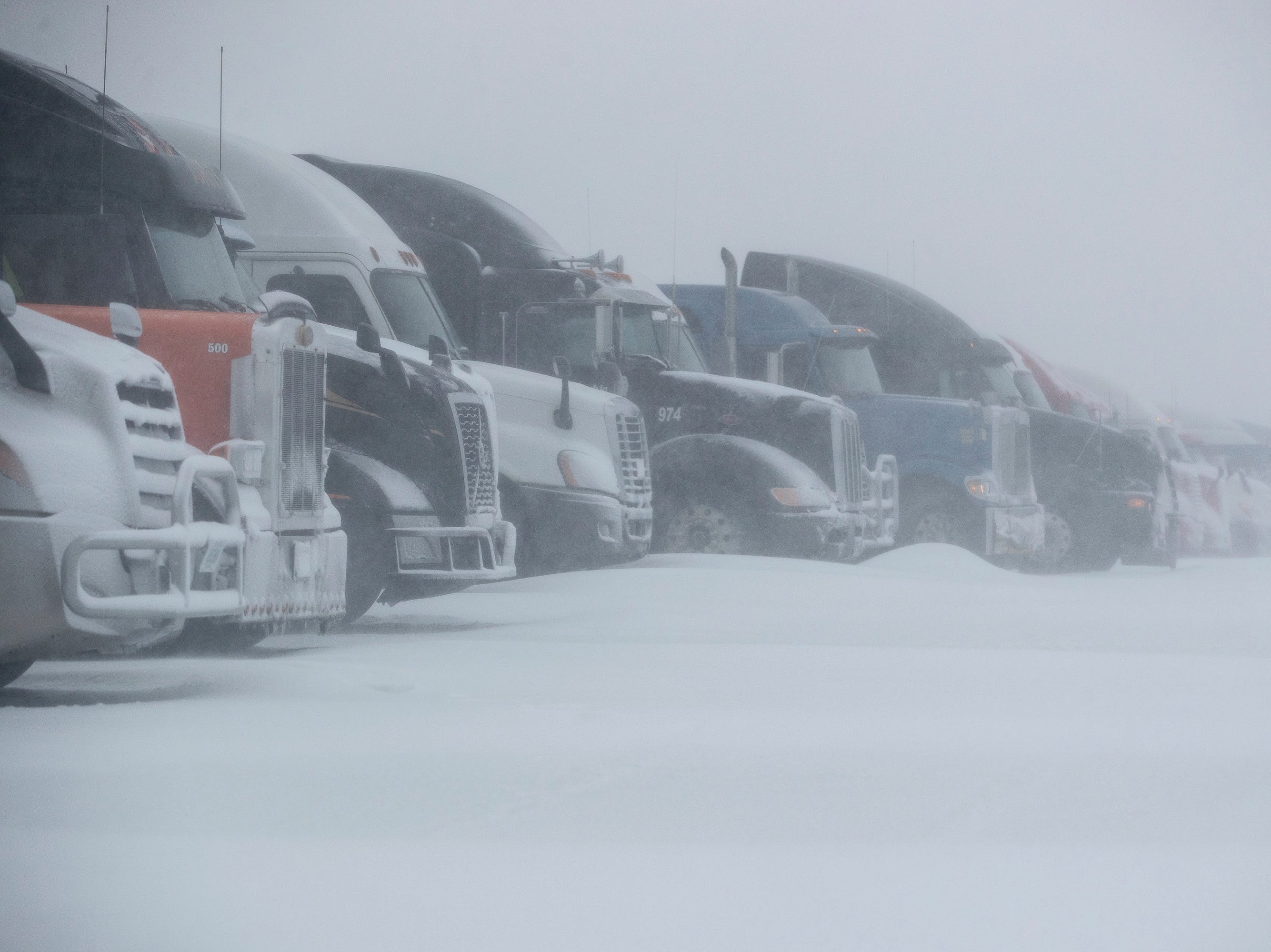 Trucks are parked in the snow at the Pilot Flying J near Interstate 90 in Rapid City, S.D., Wednesday, March 13, 2019. I-90 was closed from the Wyoming border to Oacoma, S.D., earlier in the day.