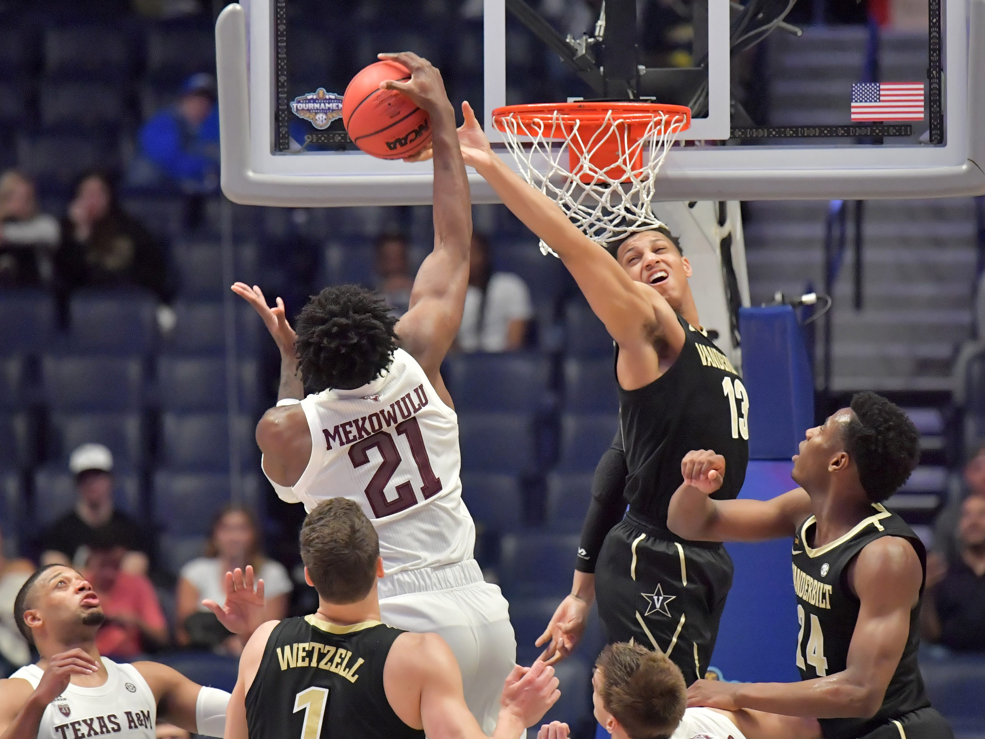 March 13: Texas A&M Aggies forward Christian Mekowulu (21) and Vanderbilt Commodores forward Matthew Moyer (13) battle for the ball in the second half of an SEC tournament game.
