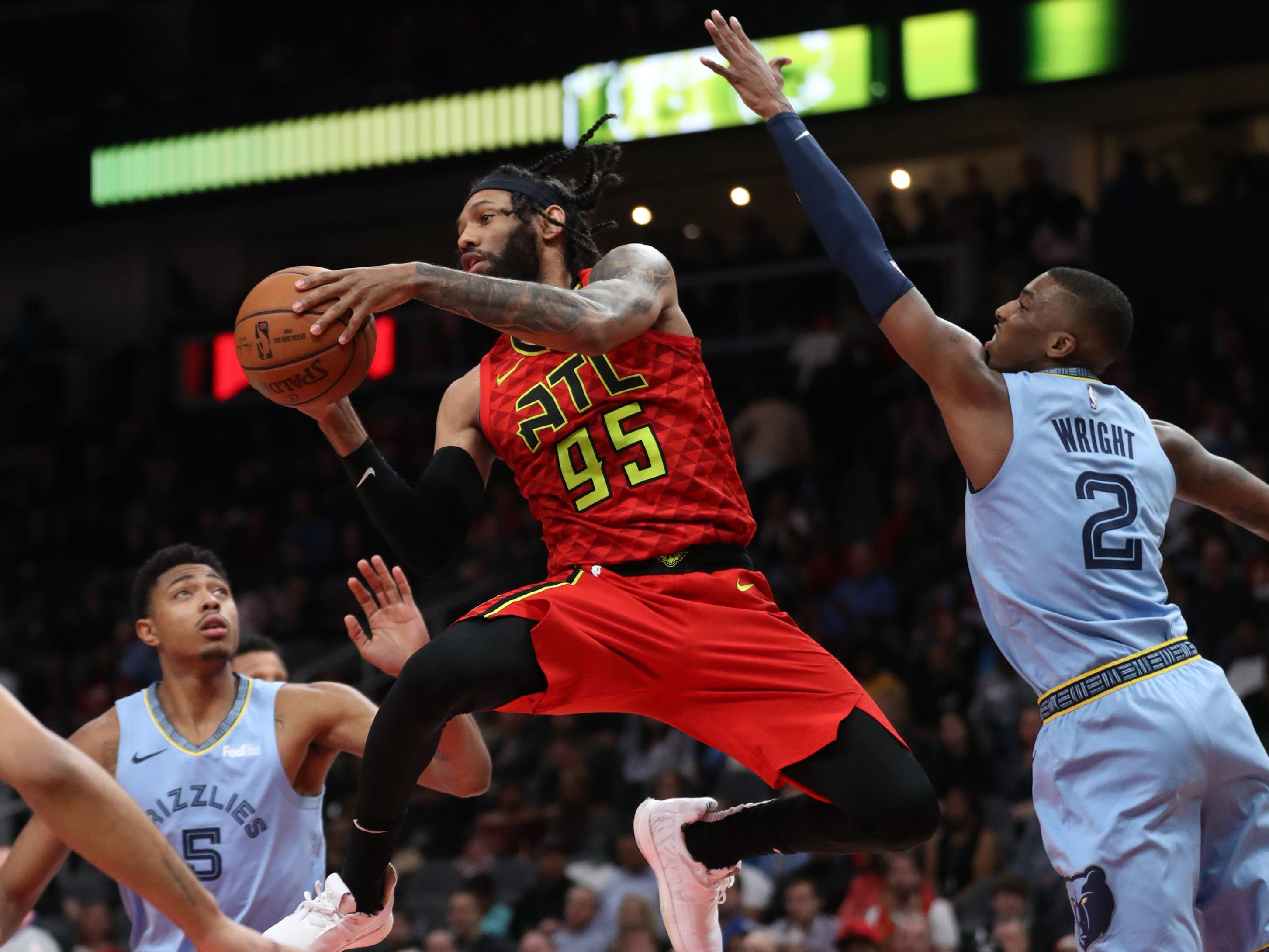 March 13: Atlanta Hawks forward DeAndre' Bembry passes out of the defense of Memphis Grizzlies guard Delon Wright (2) in the second half at State Farm Arena. The Hawks won the game, 132-111.