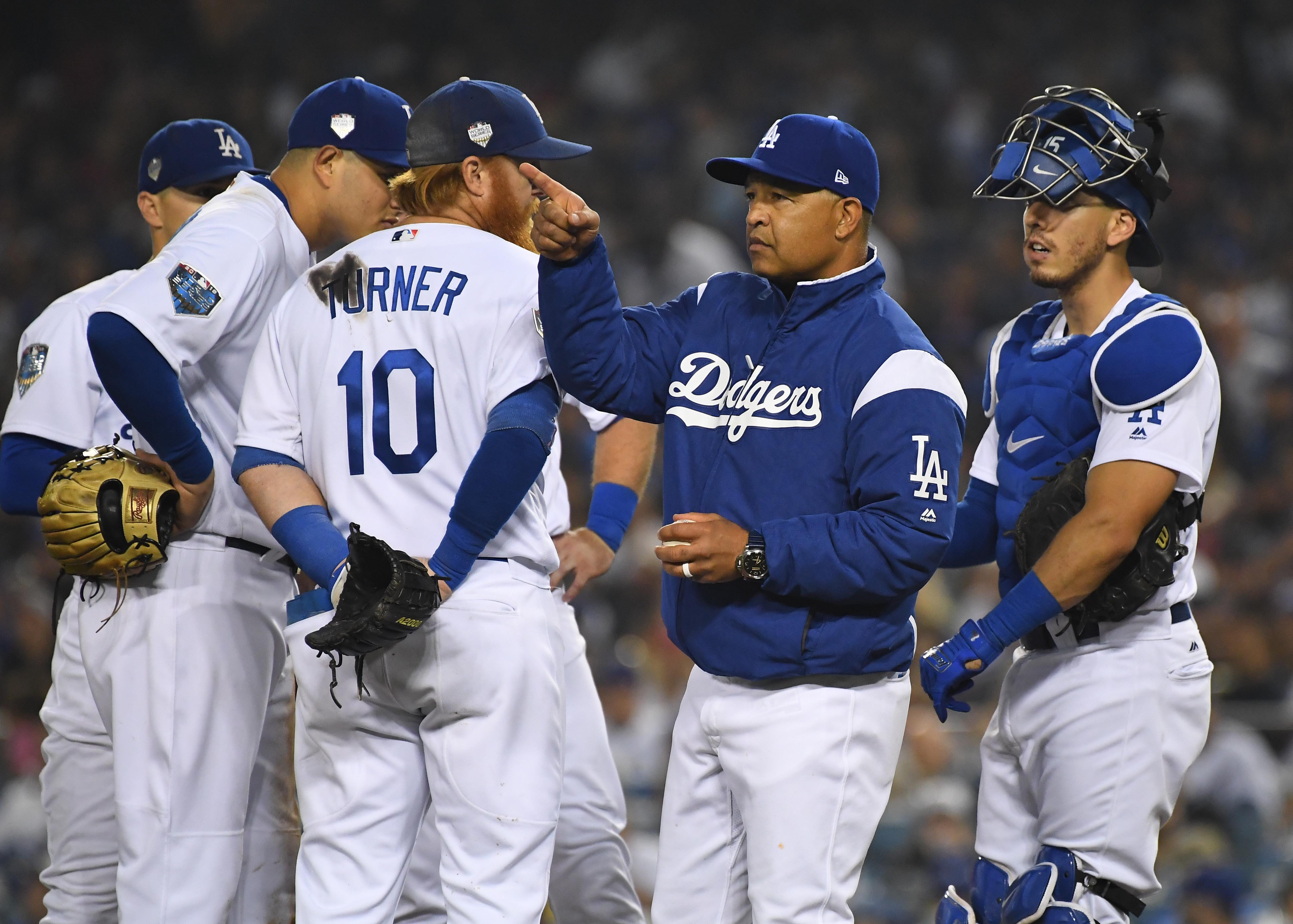 Dodgers manager Dave Roberts signals for a pitching change during a World Series.