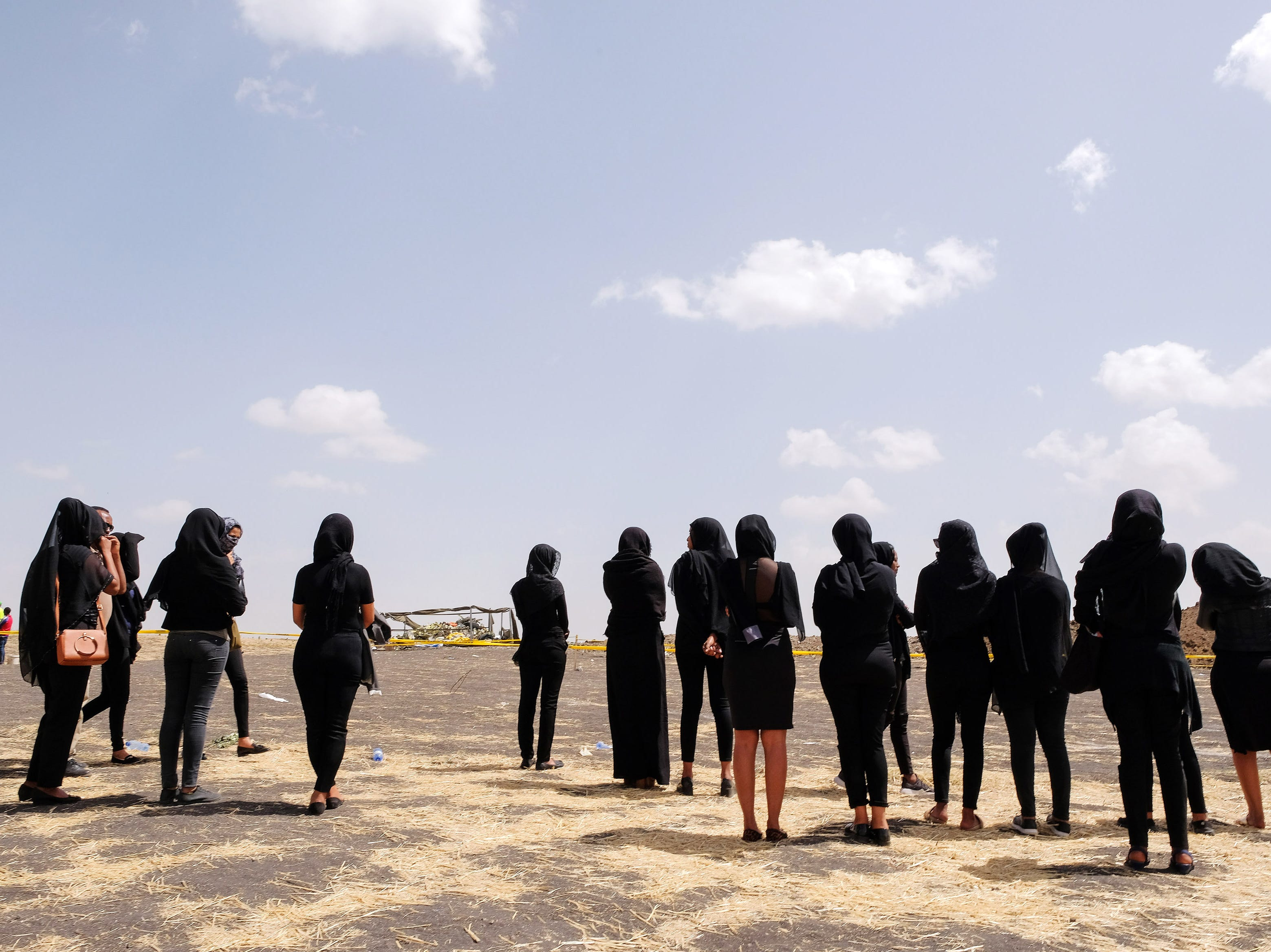 Mourners, believed to be Ethiopian Airlines cabin crew members, arrive to pay their respects at the crash site of Ethiopian Airlines Flight ET302 on March 14, 2019 in Ejere, Ethiopia. All 157 passengers and crew perished after the Ethiopian Airlines Boeing 737 Max 8 Flight came down six minutes after taking off from Bole Airport.