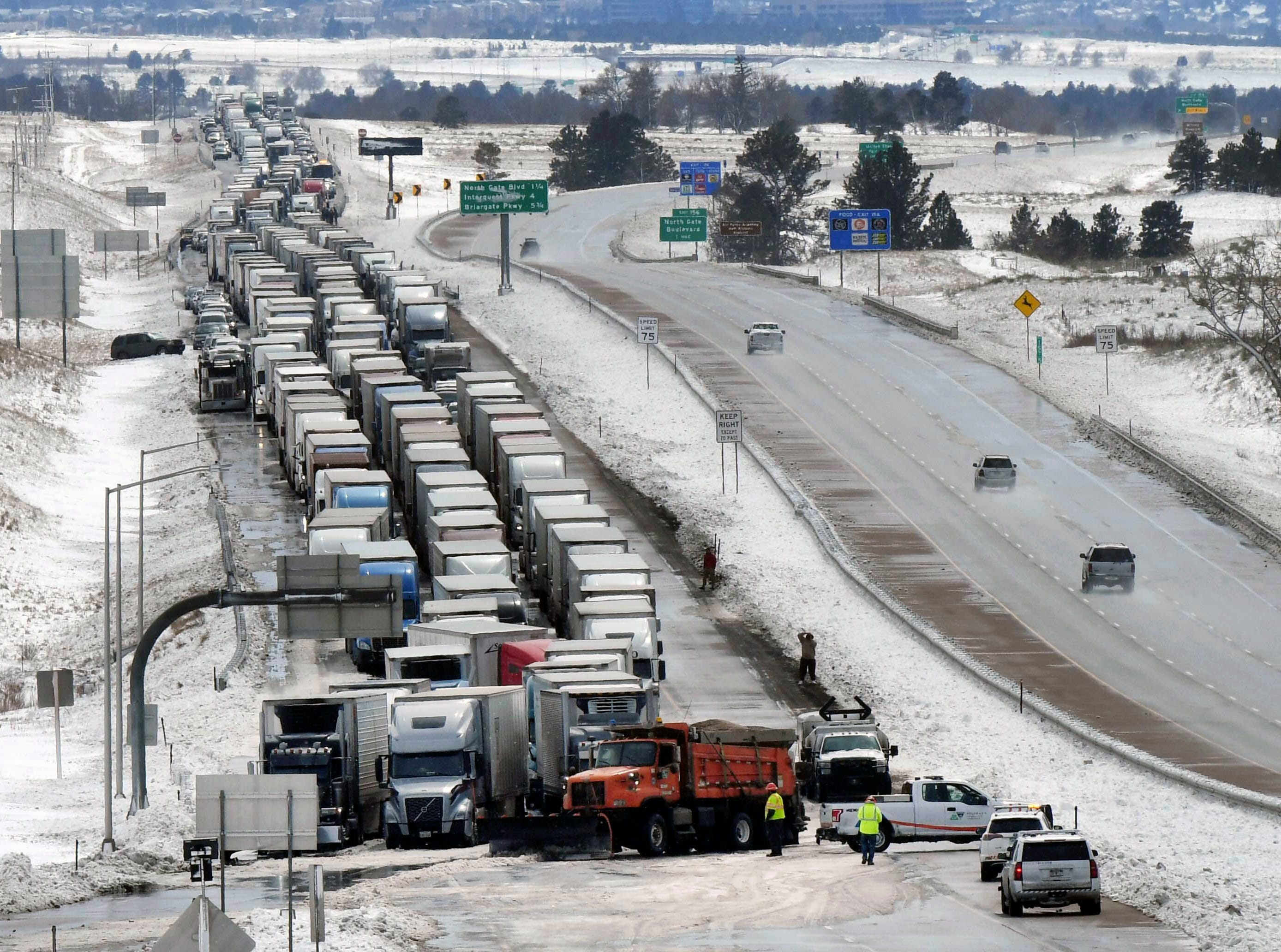 Trucks line I-25 south of Baptist Rd. Thursday, March 14, 2019 in Colorado Springs, Colo. A blizzard that paralyzed parts of Colorado and Wyoming barreled into the Midwest on Thursday, bringing whiteout conditions to western Nebraska and dumping heavy rain that prompted evacuations in communities farther east.