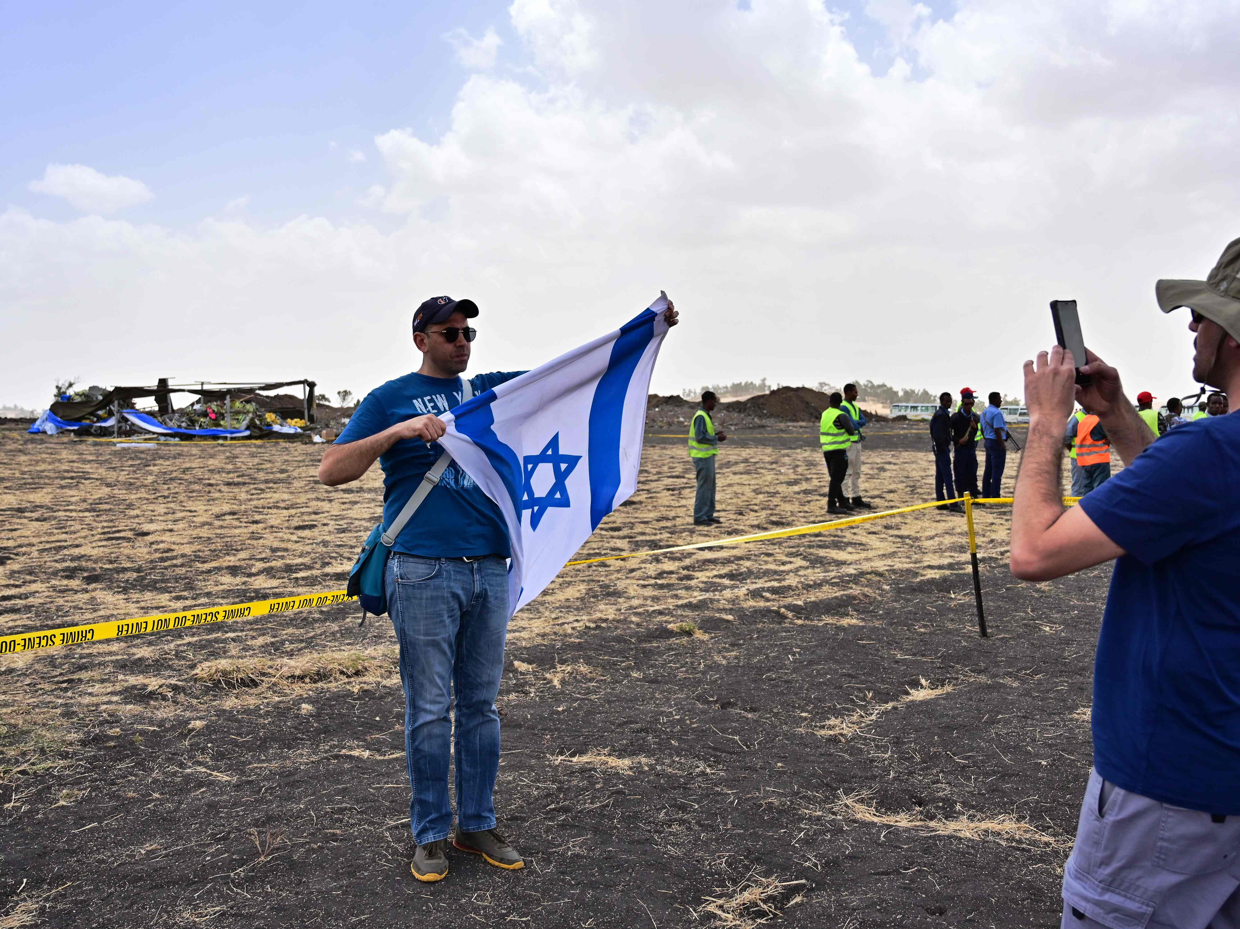 Two brothers of the Israeli victim Shimon Daniely take a photo with the Israeli flag at the crash site of the Ethiopian Airlines operated Boeing 737 MAX aircraft, at Hama Quntushele village in Oromia region, on March 14, 2019.