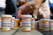 Family and friends who have lost loved ones to OxyContin and opioid overdoses leave pill bottles in protest outside the headquarters of Purdue Pharma, which is owned by the Sackler family, in Stamford, Conn., on  Aug. 17, 2018.