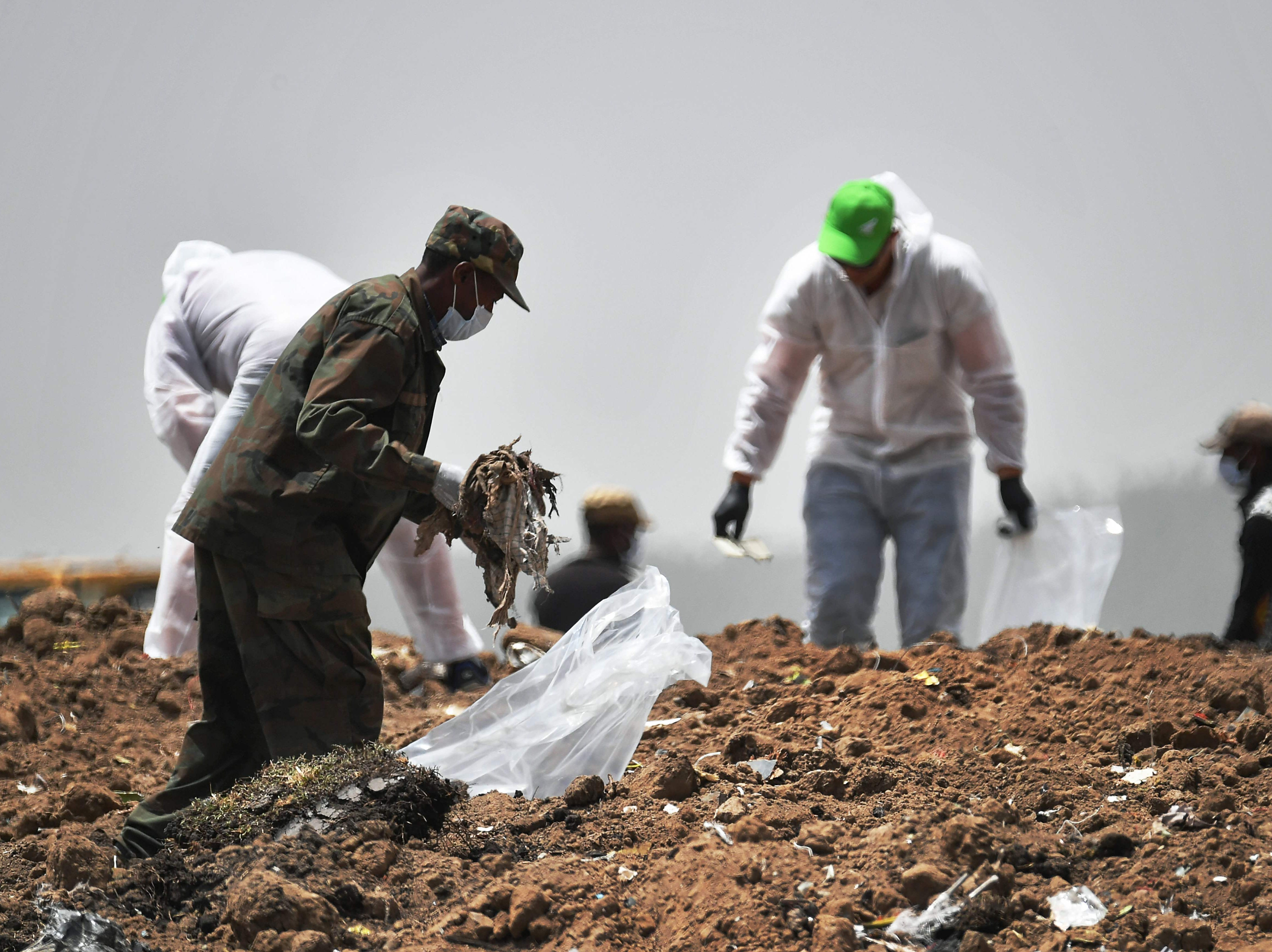 Forensics experts comb through the dirt for debris at the crash site of the Ethiopian Airlines operated Boeing 737 MAX aircraft, at Hama Quntushele village in Oromia region, on March 14, 2019, four days after the plane crashed into a field killing 157 passengers and crew. - The black box flight recorders from the Boeing 737 MAX aircraft that crashed in Ethiopia were flown to France on March 14, 2019 for analysis as the ban on the model went worldwide after the US President added the US to countries that have grounded the aircraft. The US action came after many airlines around the globe voluntarily took the model out of service and many countries banned it from their airspace.