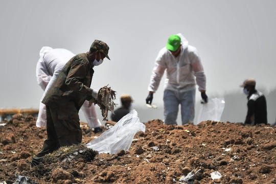 Forensics experts comb through the dirt at the crash site of an Ethiopian Airlines-operated Boeing 737 MAX aircraft at Hama Quntushele village on March 14, 2019.