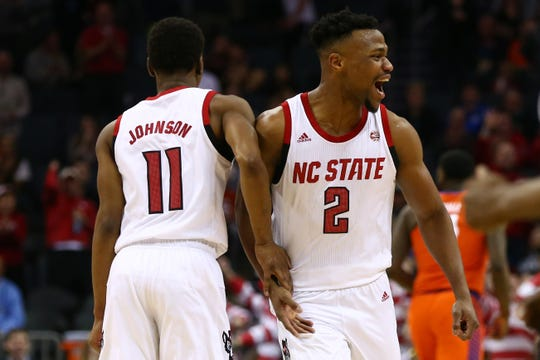 North Carolina State Wolfpack guard Torin Dorn (2) and guard Markell Johnson (11) celebrate after a basket in the second half against the Clemson Tigers in the ACC conference tournament at Spectrum Center.