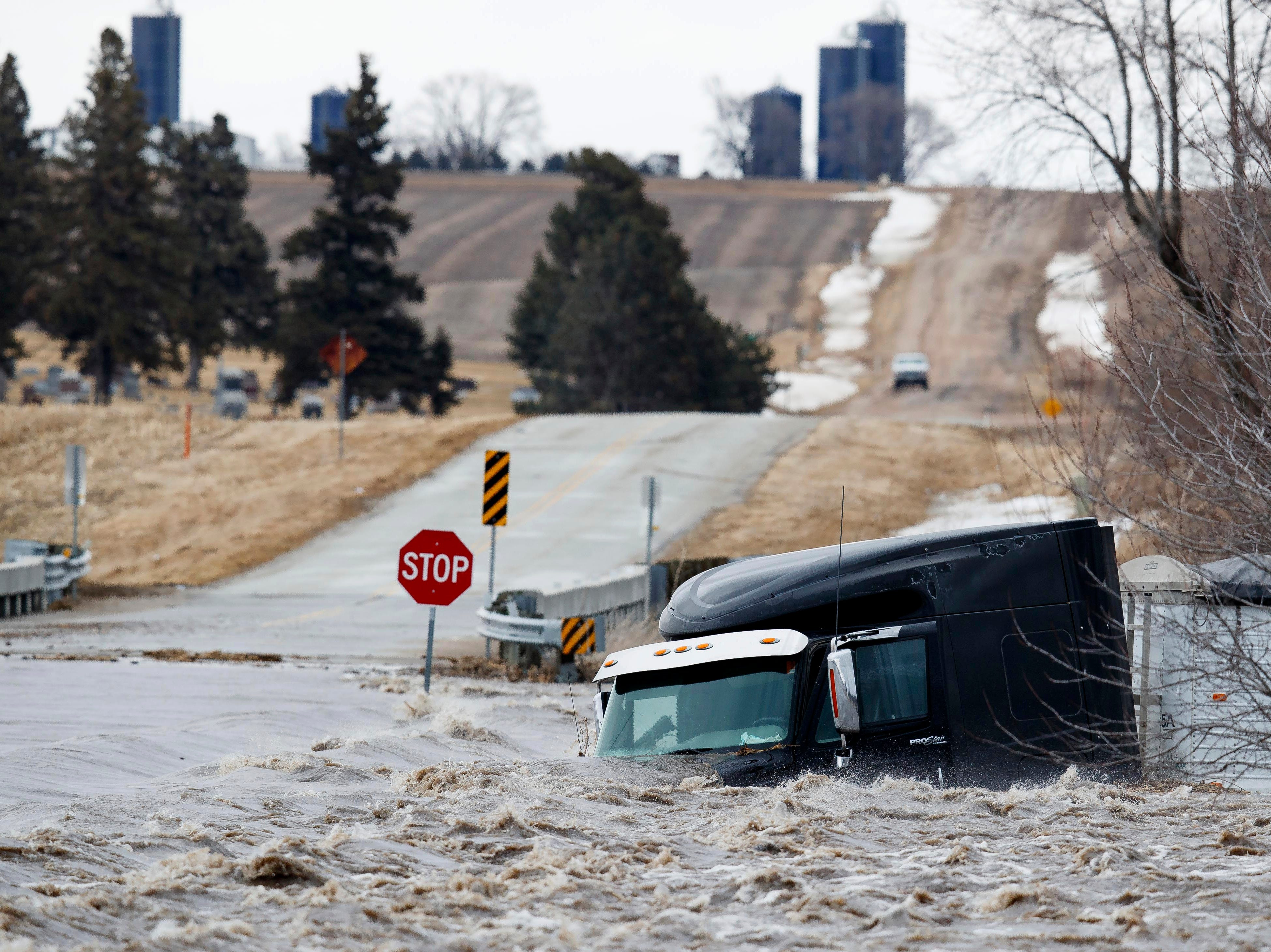 A semi truck and trailer are swept off the road by floodwaters Thursday, March 13, 2019, in Arlington, Neb. Evacuations forced by flooding have occurred in several eastern Nebraska communities, as western Nebraska residents struggled with blizzard-like conditions.