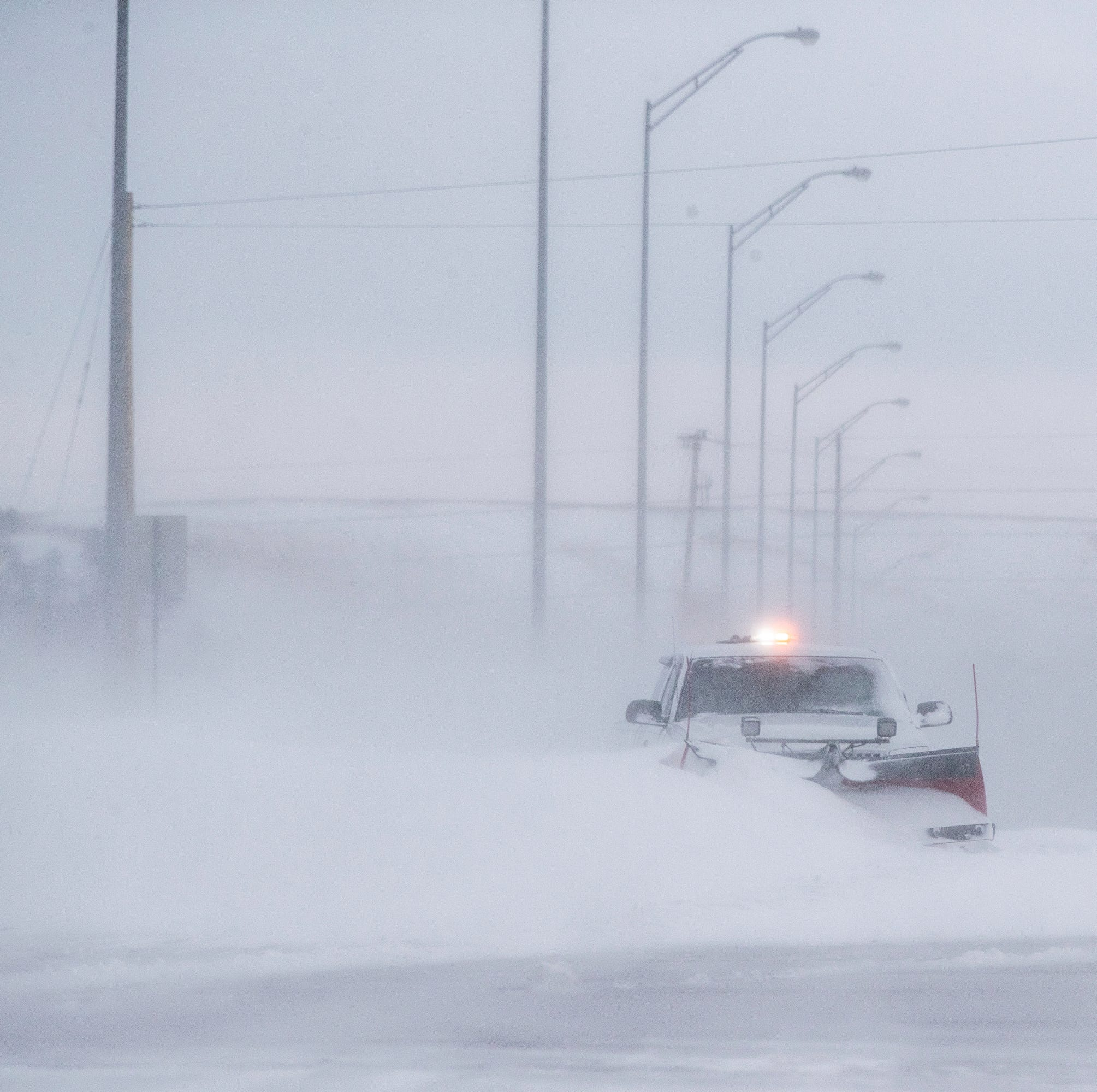 A truck with a snow plow is stuck in a snow drift on Haines Avenue in Rapid City, S.D., Thursday, March 14, 2019.  All state offices are now closed in South Dakota as blizzard conditions barrel into the Midwest.