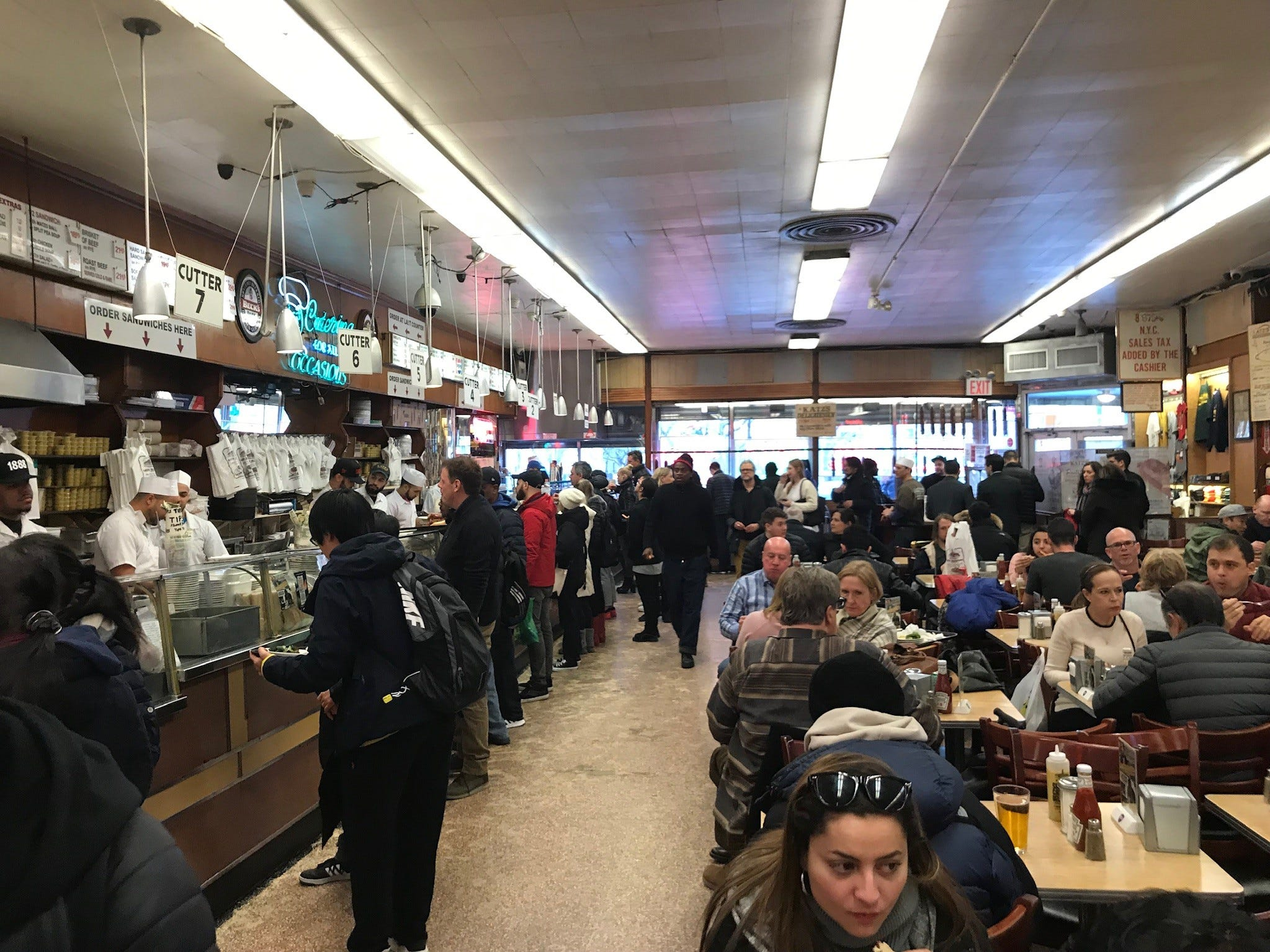 All food is ordered from stations at the very long counter along one side of the restaurant. Customers then carry their trays to the closely packed tables filling the rest of the space.