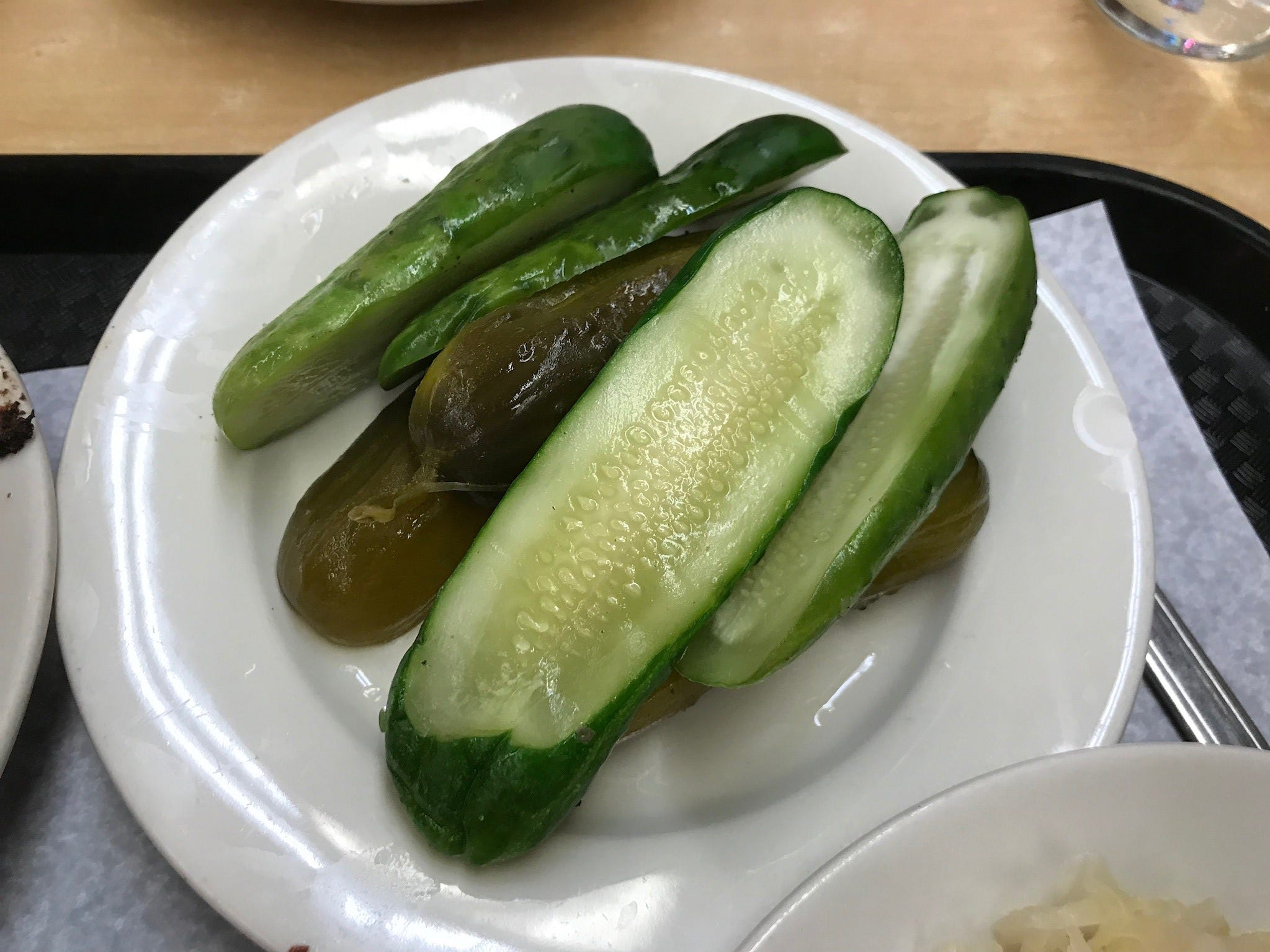"Every sandwich or meat platter comes with a generous portion of Katz's famous house-cured pickles, both full-sour (middle) and ""new,"" or half-sour, versions (bright green)."
