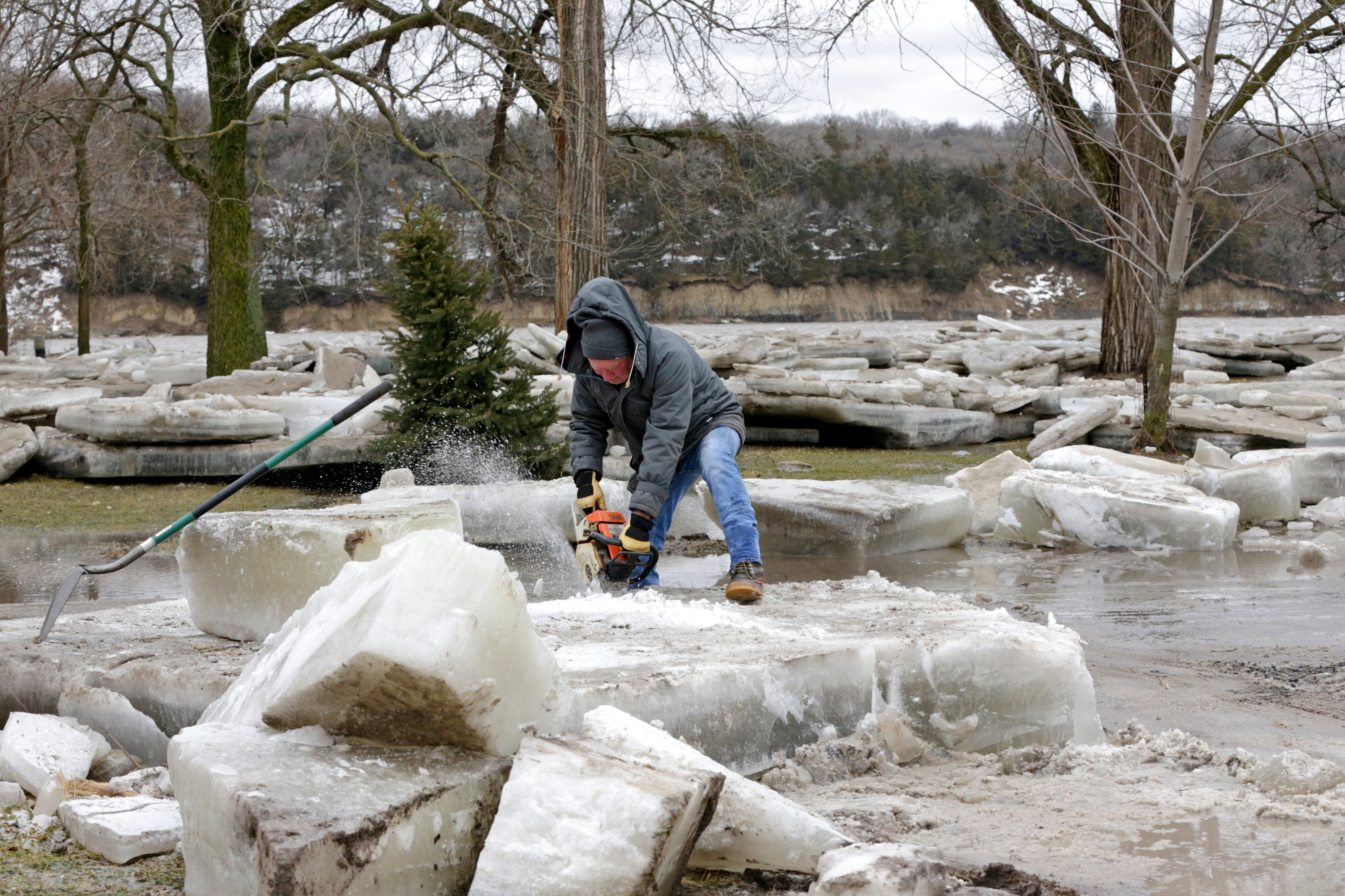 Jim Freeman tries to saw through thick ice slabs on his property in Fremont, Neb., Thursday, March 14, 2019, after the Ice-covered Platte River flooded it's banks. Evacuations forced by flooding have occurred in several eastern Nebraska communities.