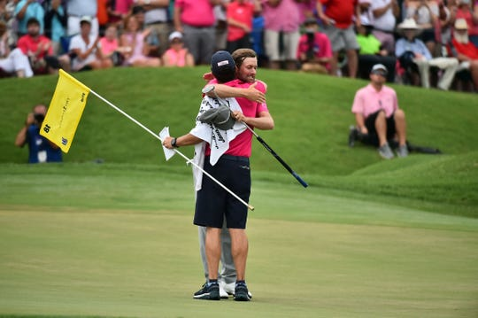 Webb Simpson celebrates with his caddie Paul Tesori on the 18th green after winning the The Players Championship on May 13, 2018.