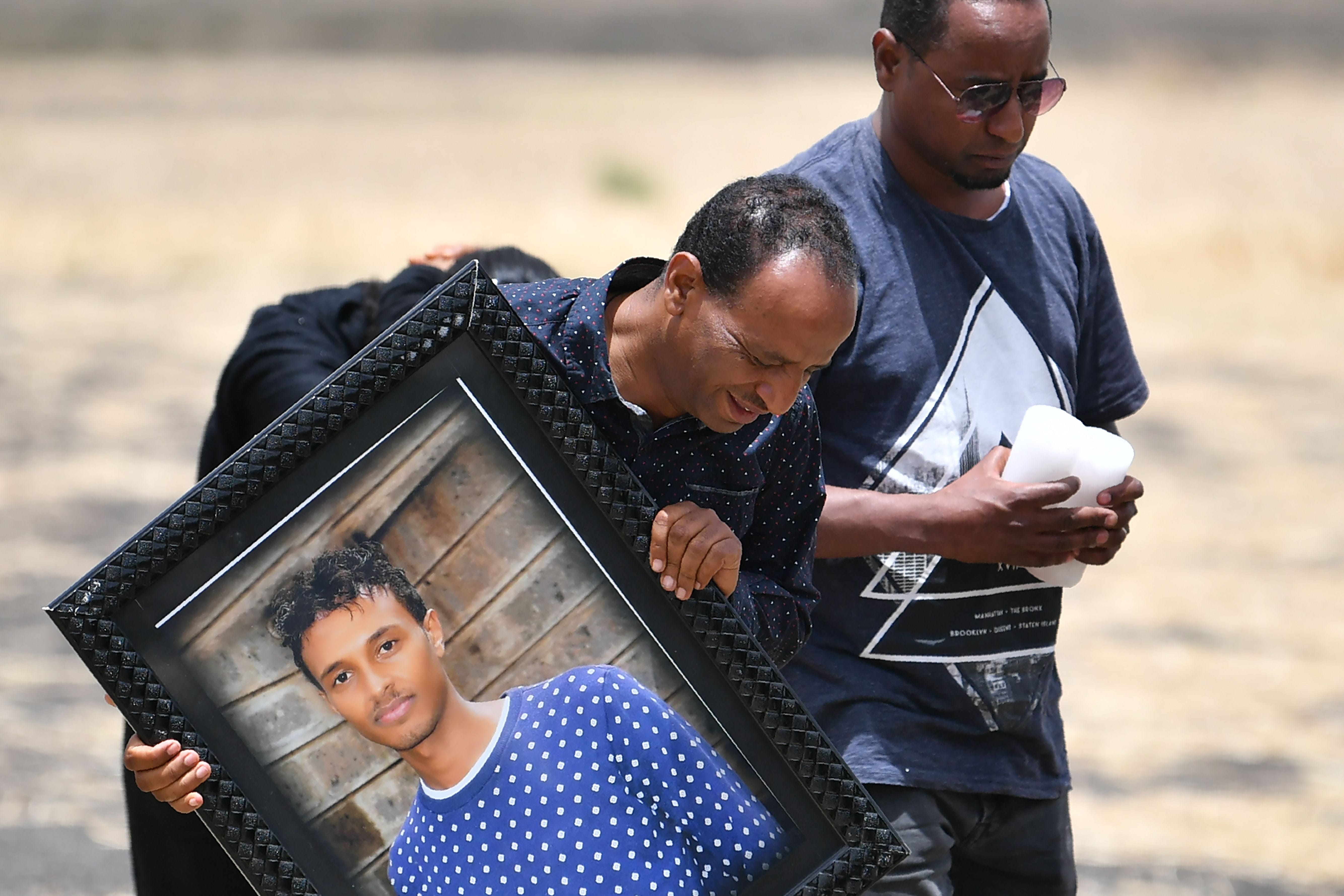 A grieving relative carries the picture of a victim at the crash site of the Ethiopian Airlines operated Boeing 737 MAX aircraft, at Hama Quntushele village in Oromia region, on March 14, 2019.