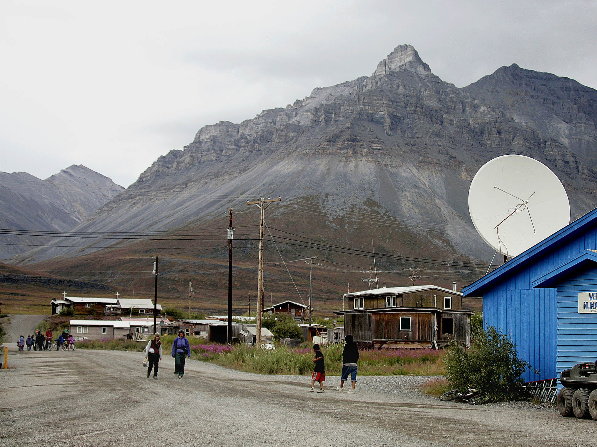 ** FOR IMMEDIATE RELEASE--ONE OF FIFTEEN PHOTOS BY AP PHOTOGRAPHER AL GRILLO **Villagers and visitors walk the dirt road past the Nunamiut  store in Anaktuvuk Pass, Alaska, Aug. 9, 2005.  The village, with some 300 residents, is the only community within the Gates of the Arctic National Park and one of the rare villages with a museum. The Simon Paneak Memorial Museum offers a comprehensive look at a once-nomadic people, as well as local artwork for sale, including caribou skin masks trimmed with wolf, fox or bear fur.  (AP Photo/Al Grillo) ORG XMIT: NY422
