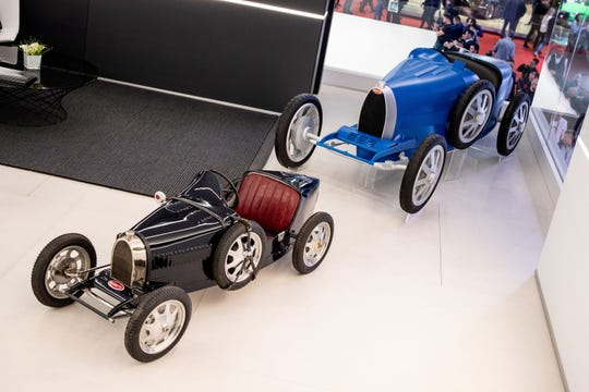 The original Bugatti Baby (black) was a child's toy. The new Bugatti Baby II (blue) is larger and suitable for both kids and adults.