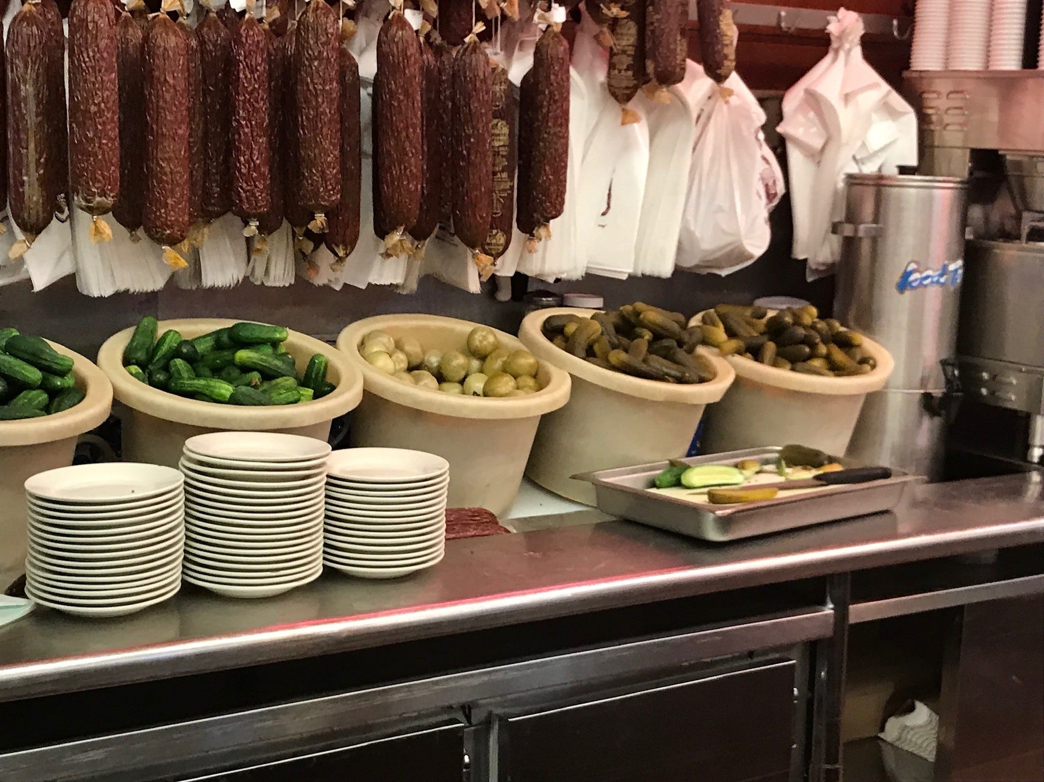 Salamis, pickles and pickled green tomatoes wait to be dispensed from behind the counter.