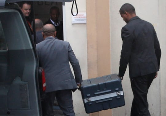 Two men carry suitcases containing the flight recorders from the Ethiopian jet into the French air accident investigation authority on March 14, 2019, in Le Bourget, north of Paris.