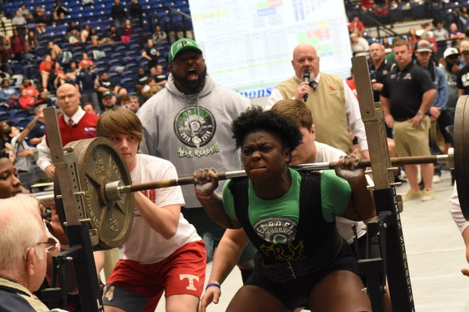 Peabody coach Jesse Esters (back) encourages lifter Taina Caldwell as she squats 455 pounds setting a new state record during the 2019 Allstate Sugar Bowl LHSAA Powerlifting State Championships held at the Rapides Parish Coliseum.