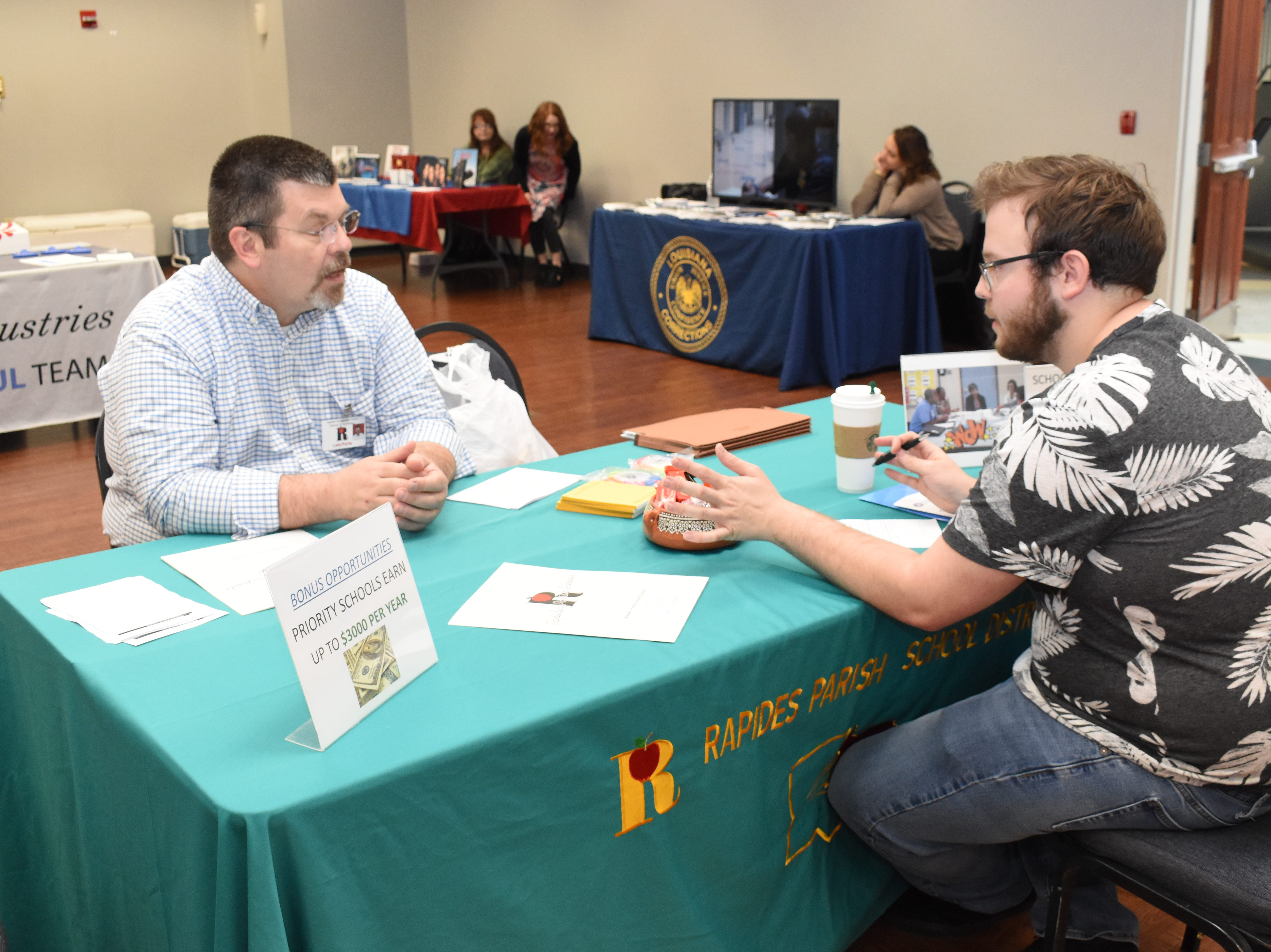 Luke Purdy (left), director of technology for the Rapides Parish School Board, talks with Louisiana College senior journalism major Brandon Murphy at a career fair held Thursday, March 14, 2019 at Louisiana College. About 34 area businesses participated in the fair. Those included law enforcement, education, health care and retail.