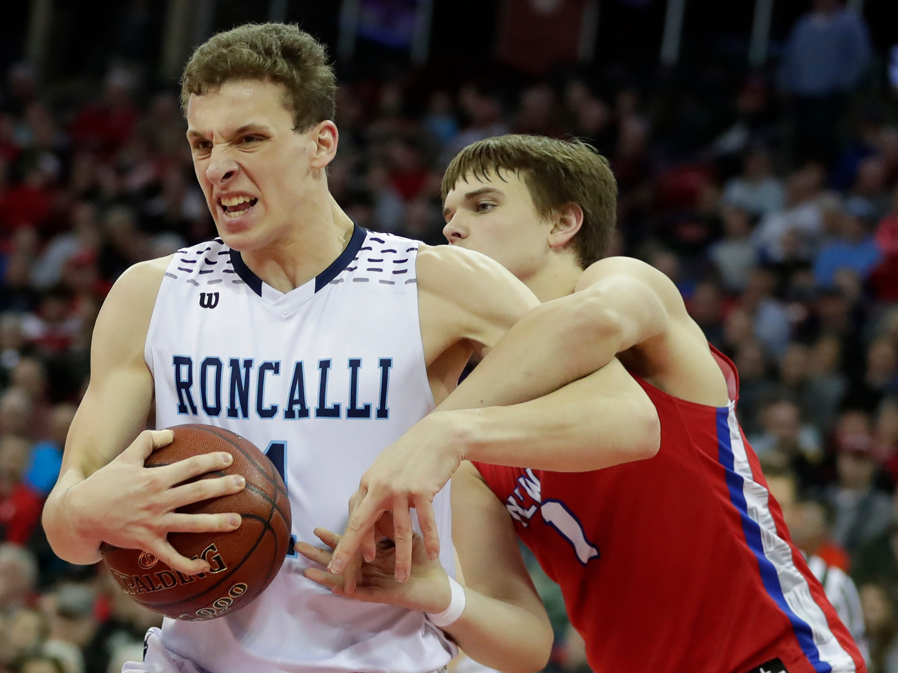 Roncalli High School's Daniel Burgarino (1) fends off New Glarus High School's Mason Martinson (1) for control of the ball during their WIAA Division 4 boys basketball state semifinal at the Kohl Center Thursday, March 14, 2019, in Madison, Wis.