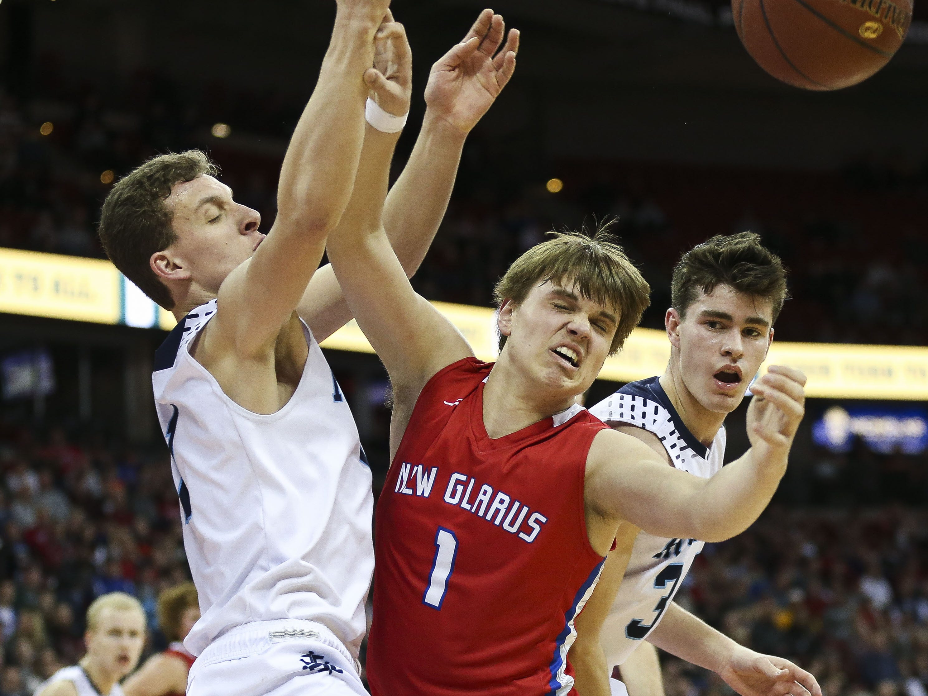 Roncalli High School's Daniel Burgarino (1) and New Glarus High School's Mason Martinson (1) fight for a rebound in a Division 4 boys basketball state semifinal on Thursday, March 14, 2019, at the Kohl Center in Madison, Wis. New Glarus won the game, 44-41, to advance to Saturday's championship game. Tork Mason/USA TODAY NETWORK-Wisconsin