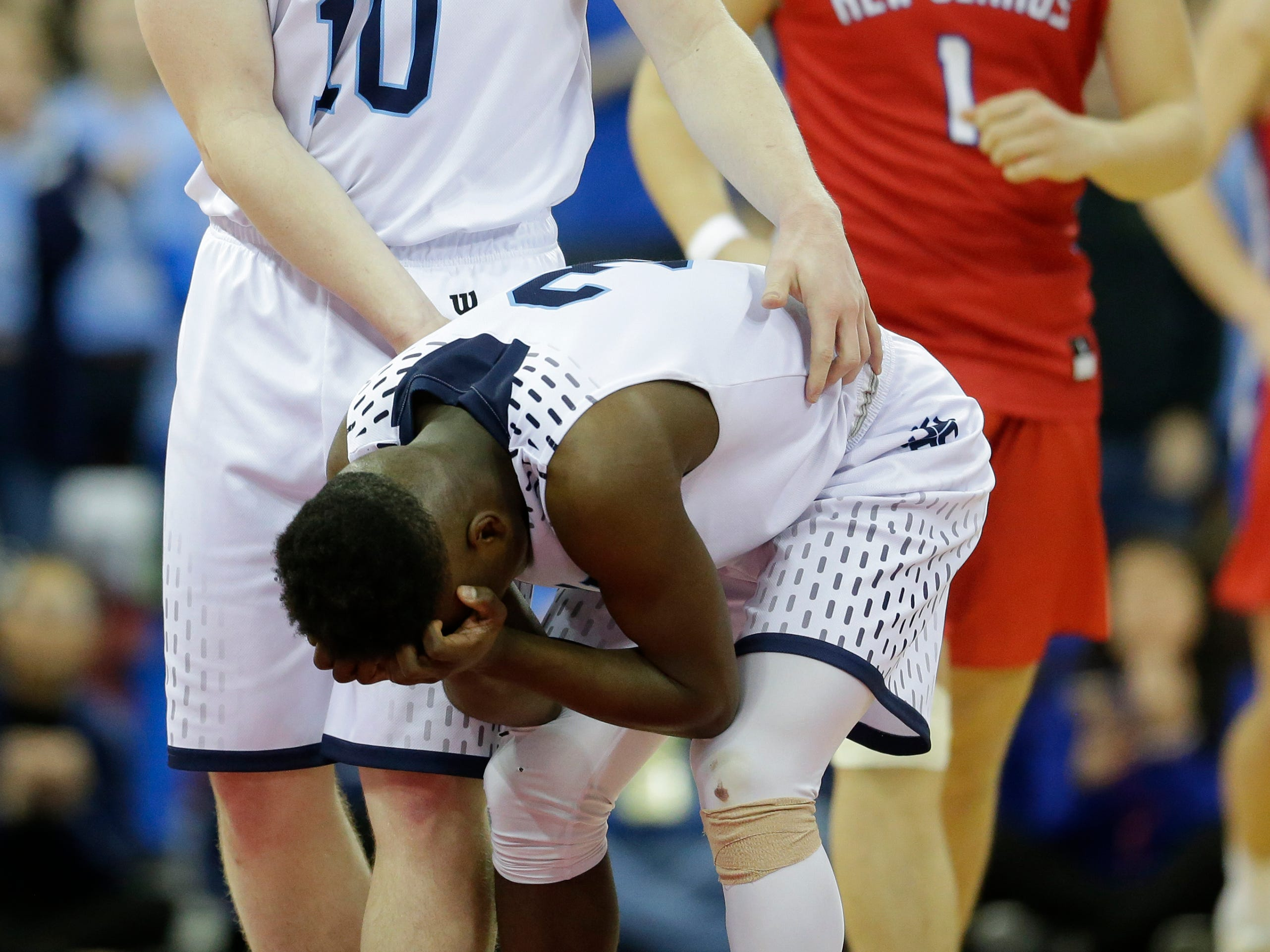 Roncalli High School's Matthew Le Vene (10) consoles teammate Chombi Lambert (3) after he misses a shot that would've put the Jets in the lead against New Glarus High School in final minute oftheir WIAA Division 4 boys basketball state semifinal at the Kohl Center Thursday, March 14, 2019, in Madison, Wis. New Glarus defeated Roncalli 44-41.