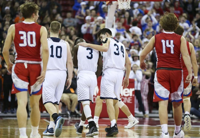 Roncalli's Ian Behringer (34) consoles Chombi Lambert (3) after Lambert missed a would-be game-tying 3-pointer in the closing seconds against New Glarus on Thursday in a Division 4 boys basketball state semifinal at the Kohl Center in Madison.