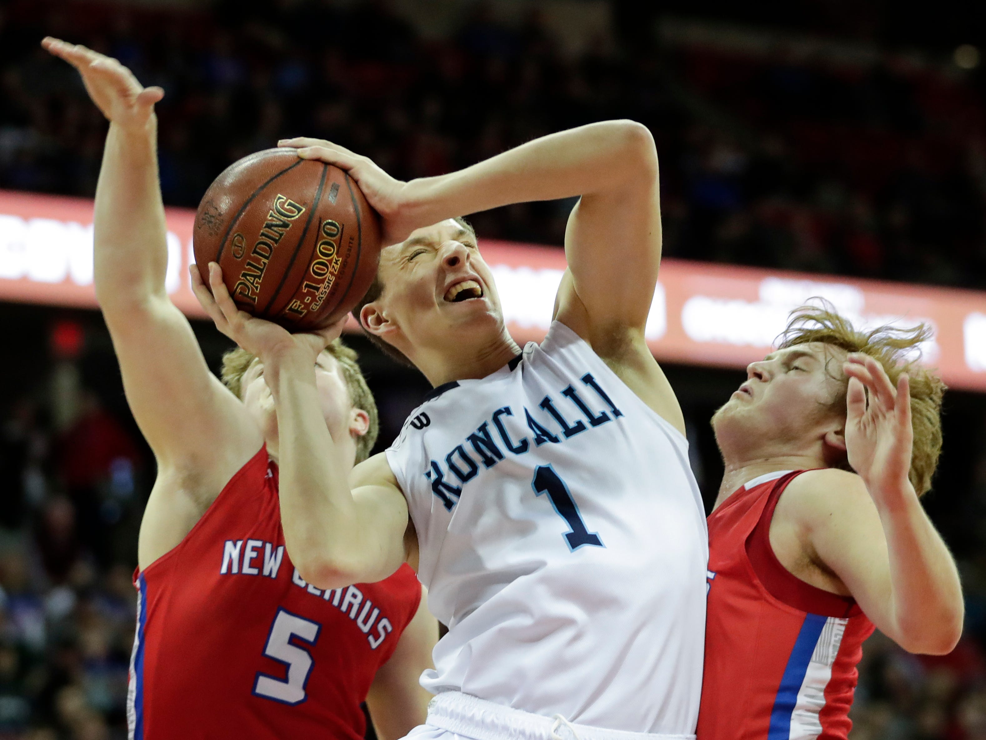 Roncalli High School's Daniel Burgarino (1) goes up for a shot against New Glarus High School during their WIAA Division 4 boys basketball state semifinal at the Kohl Center Thursday, March 14, 2019, in Madison, Wis.