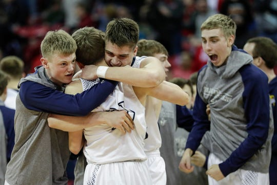 Columbus Catholic teammates hug Tom Nystrom (21) after he hit the game-winning 3-pointer to defeat Bangor in a WIAA Division 5 boys basketball state semifinal at the Kohl Center on Friday in Madison.